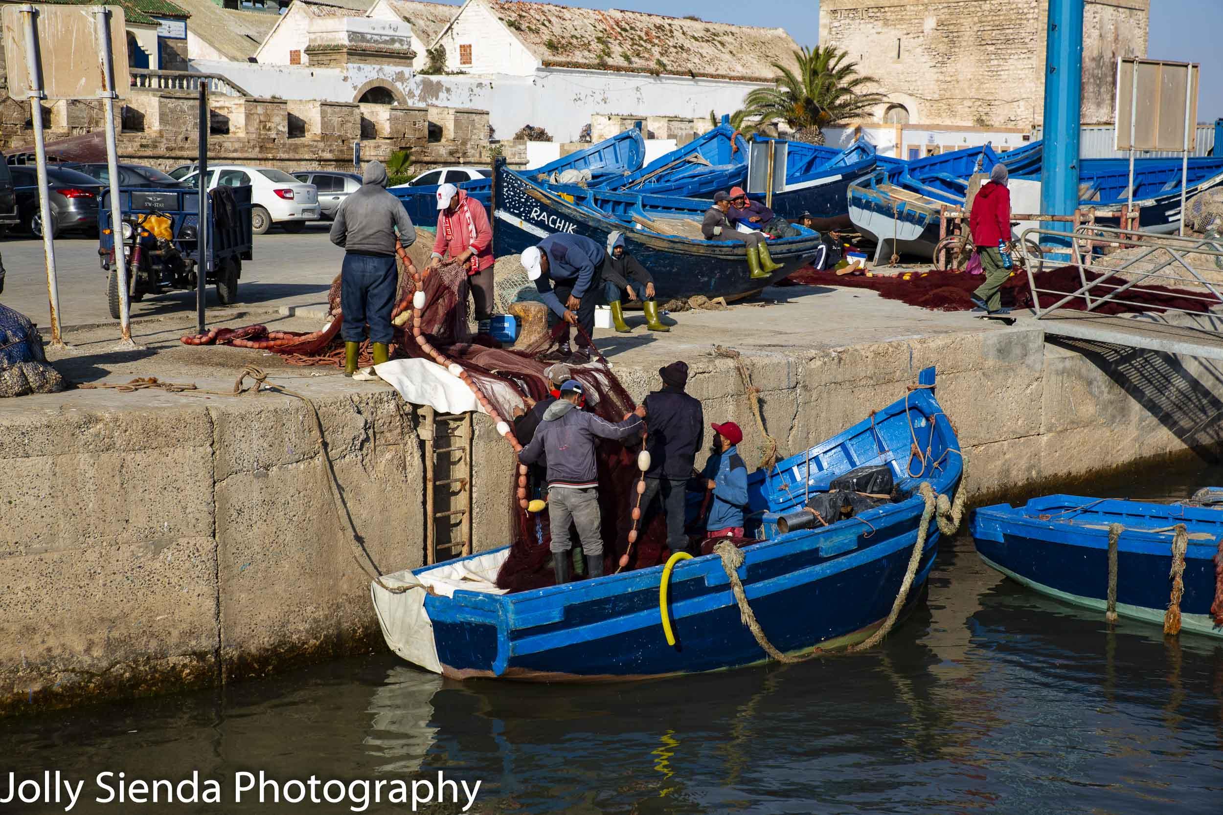 Fishermen hoist nets into the wooden boats