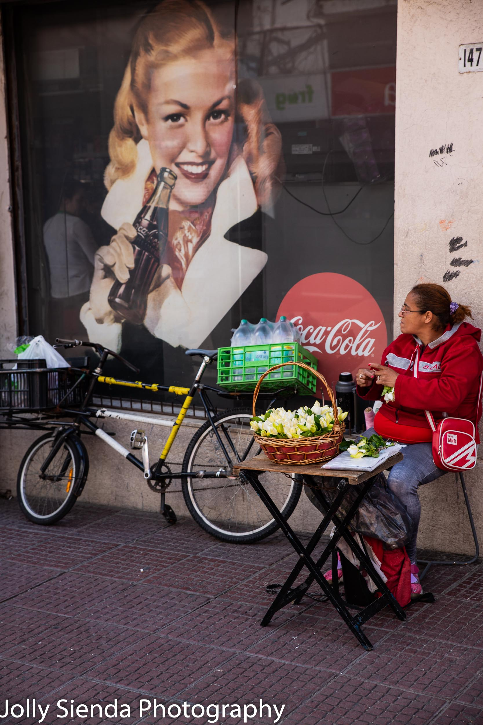 Woman selling vegetables and a Coca Cola sign