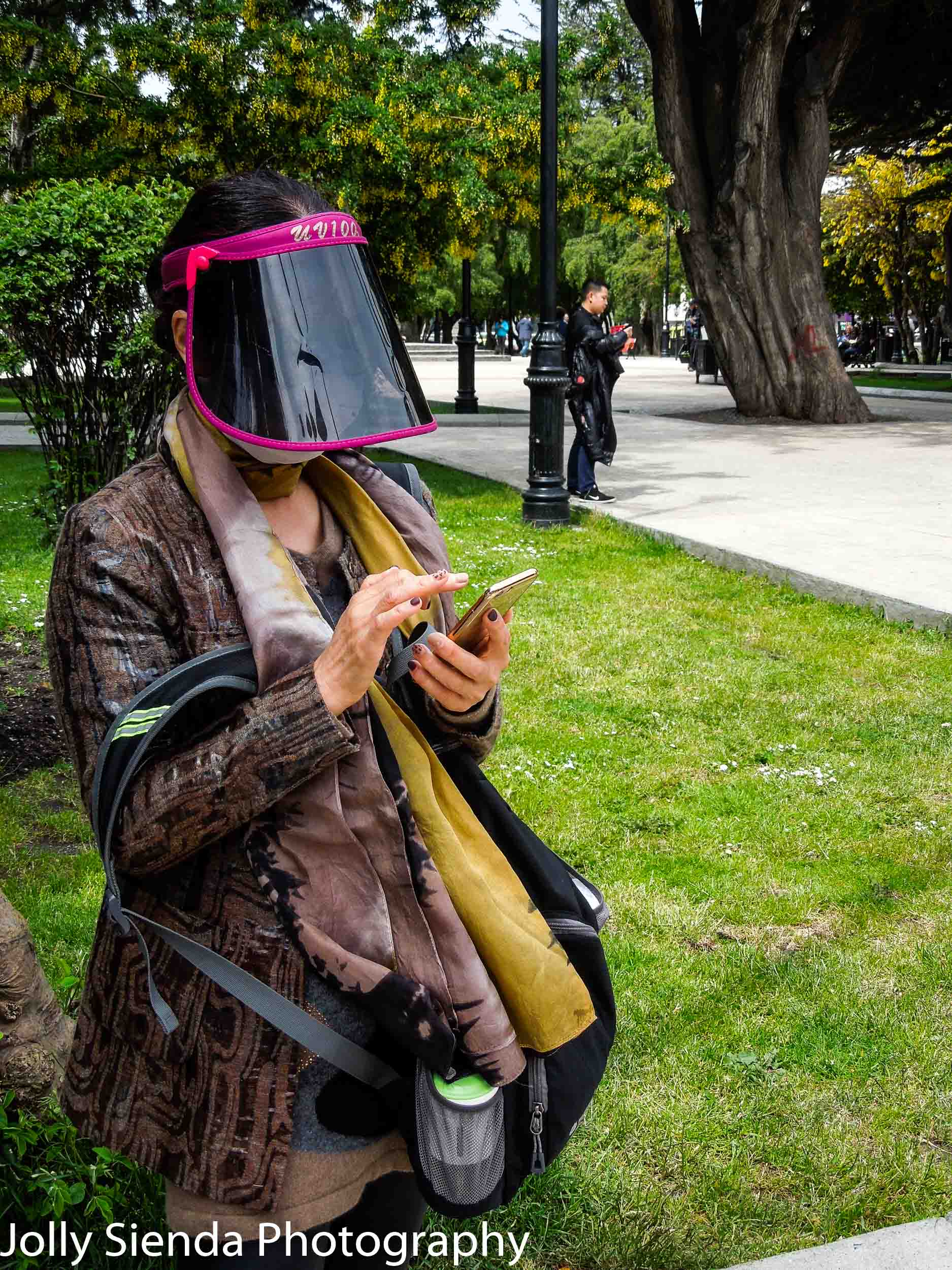 Woman wears a plastic shield mask over her face as she checks he