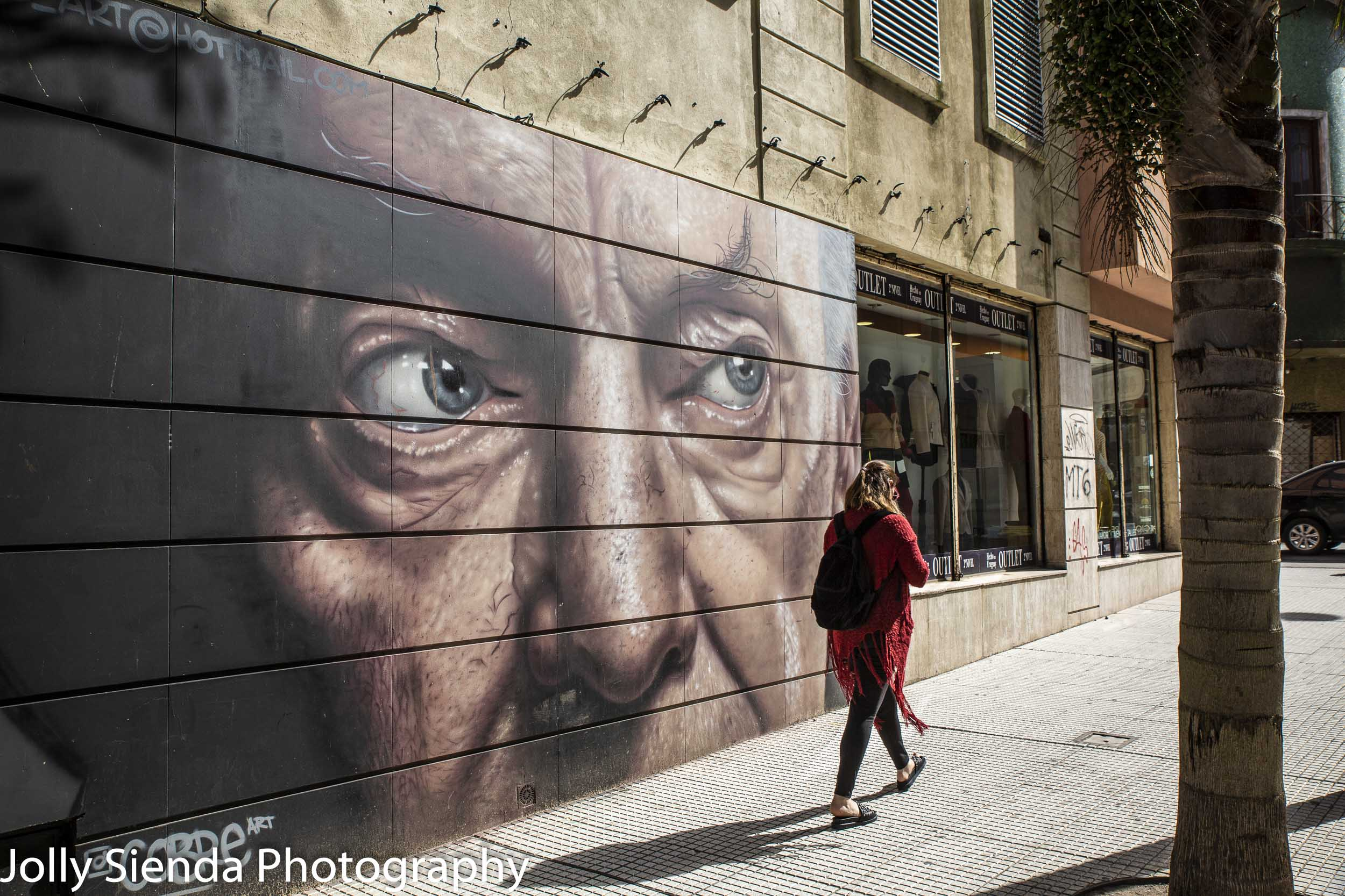 Lady in red walks past an art mural, Montevideo, Uruguay