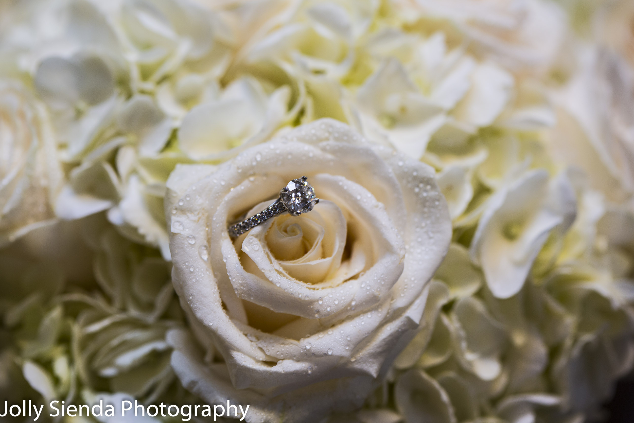 Princess cut diamond ring on the brides white rose bouquet