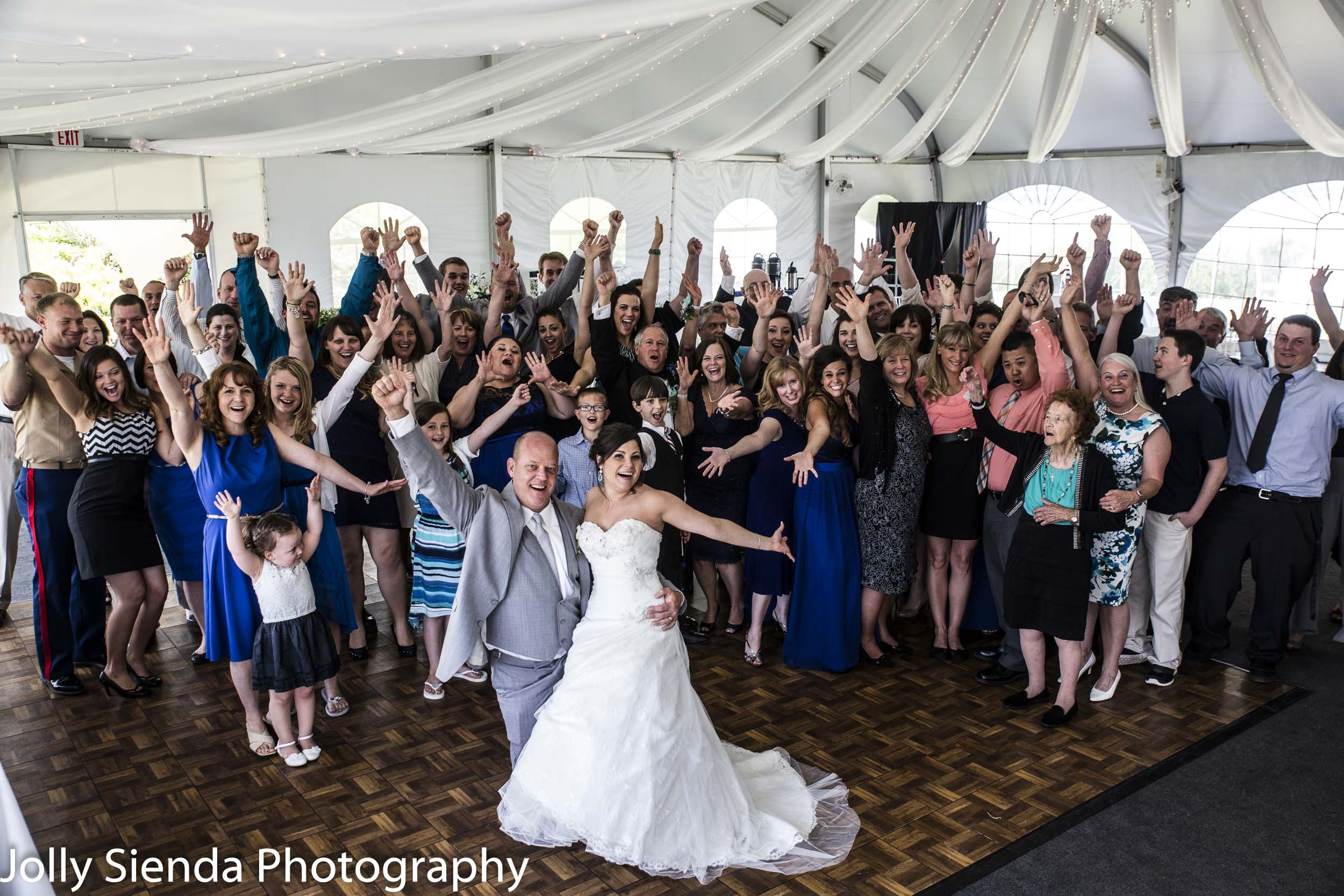 Wedding reception with large group, under a pavilion, with an aerial photograph of the bride, groom, and their guests.