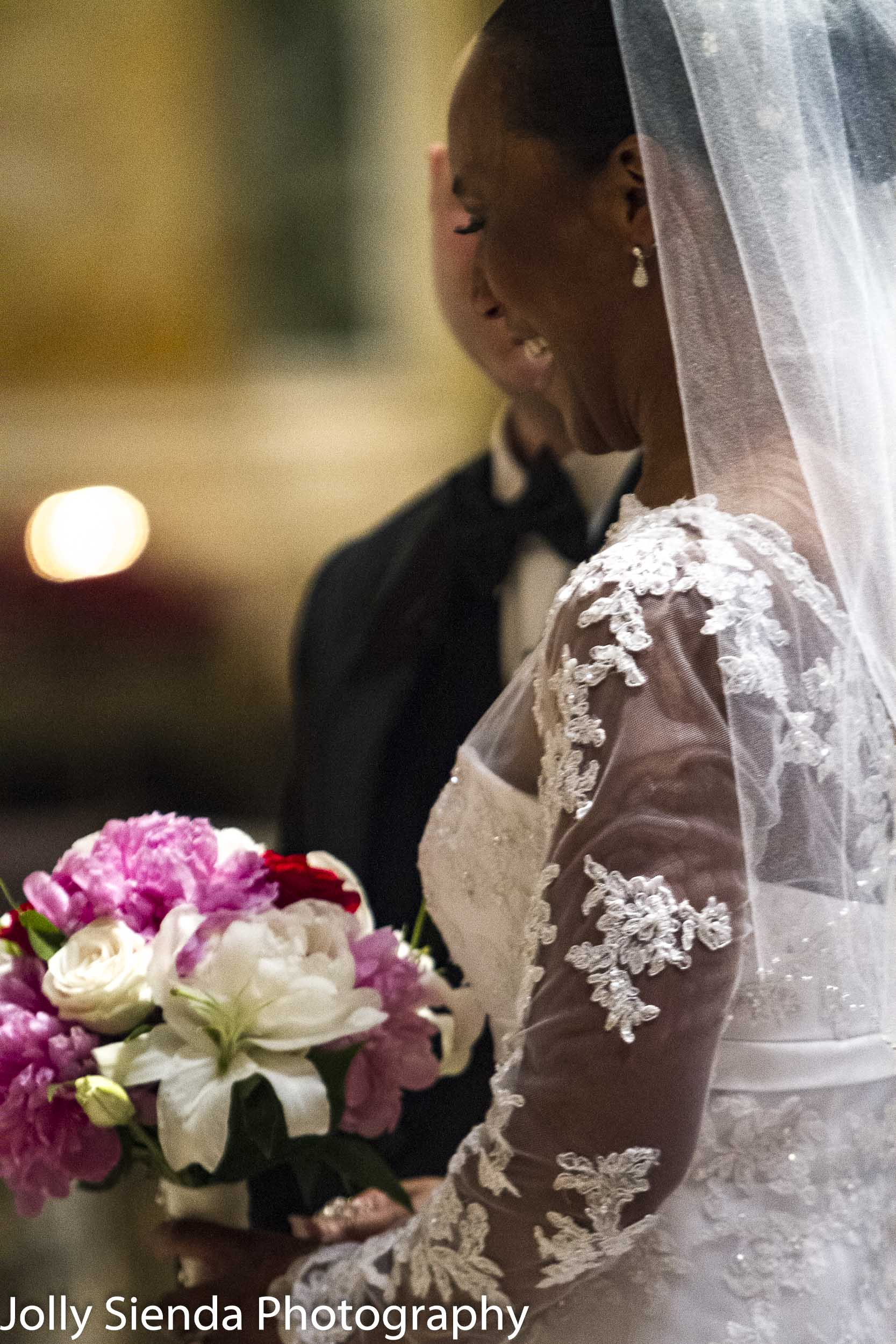 Glamourous bride with bouquet at the alter