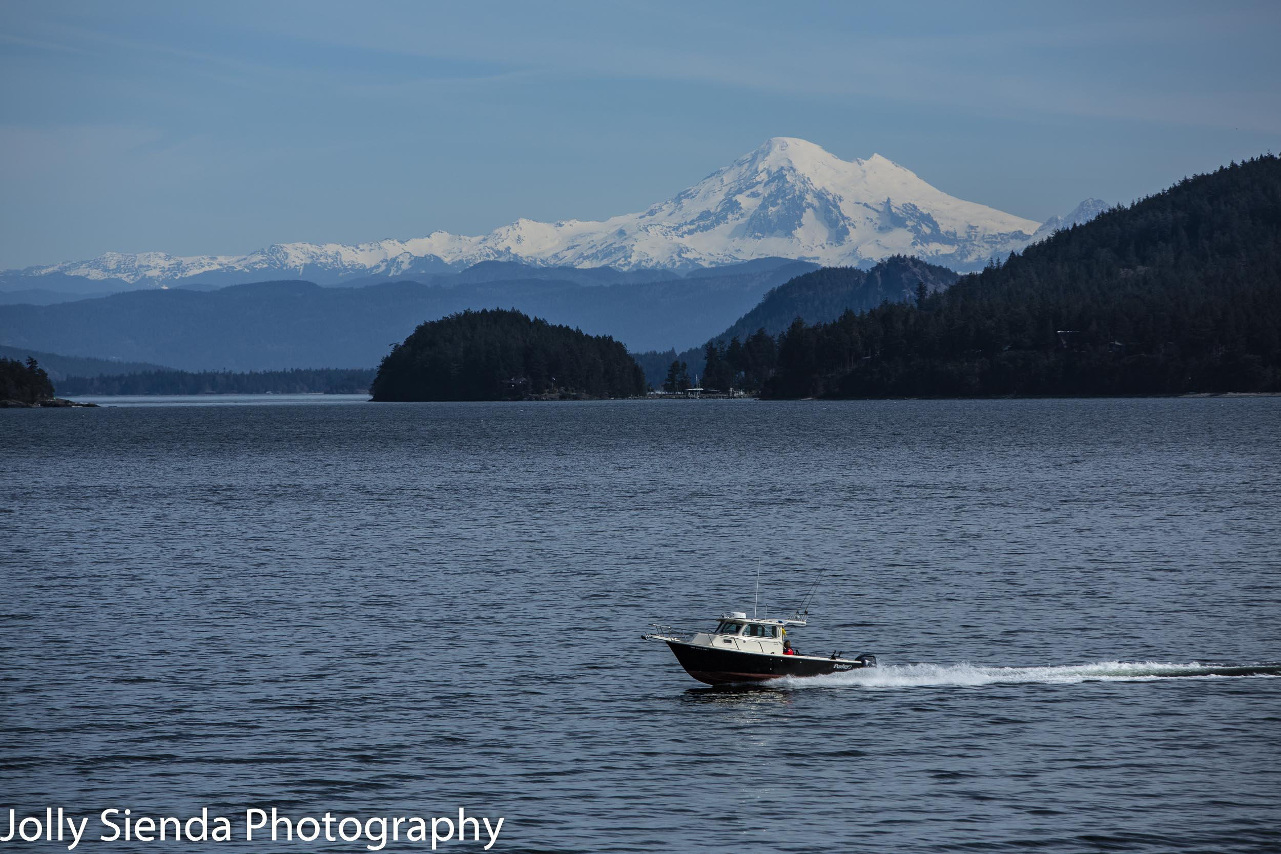Speed boat cruises through the San Juan Island archipelago with Mount Baker in the background.