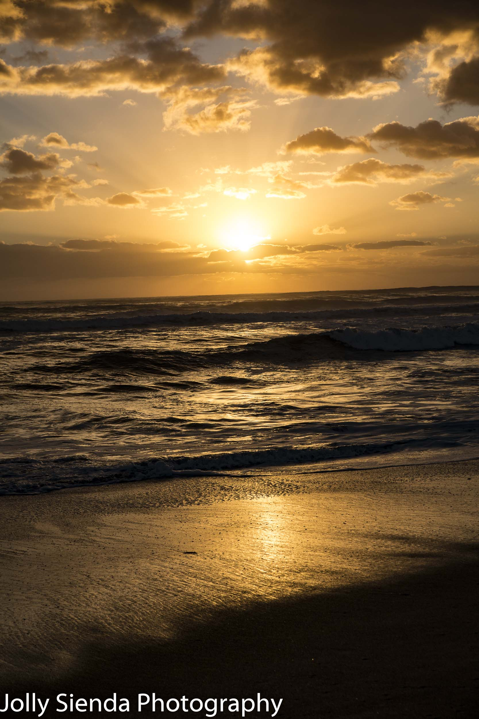 Sunrise amd waves over a wet sandy beach