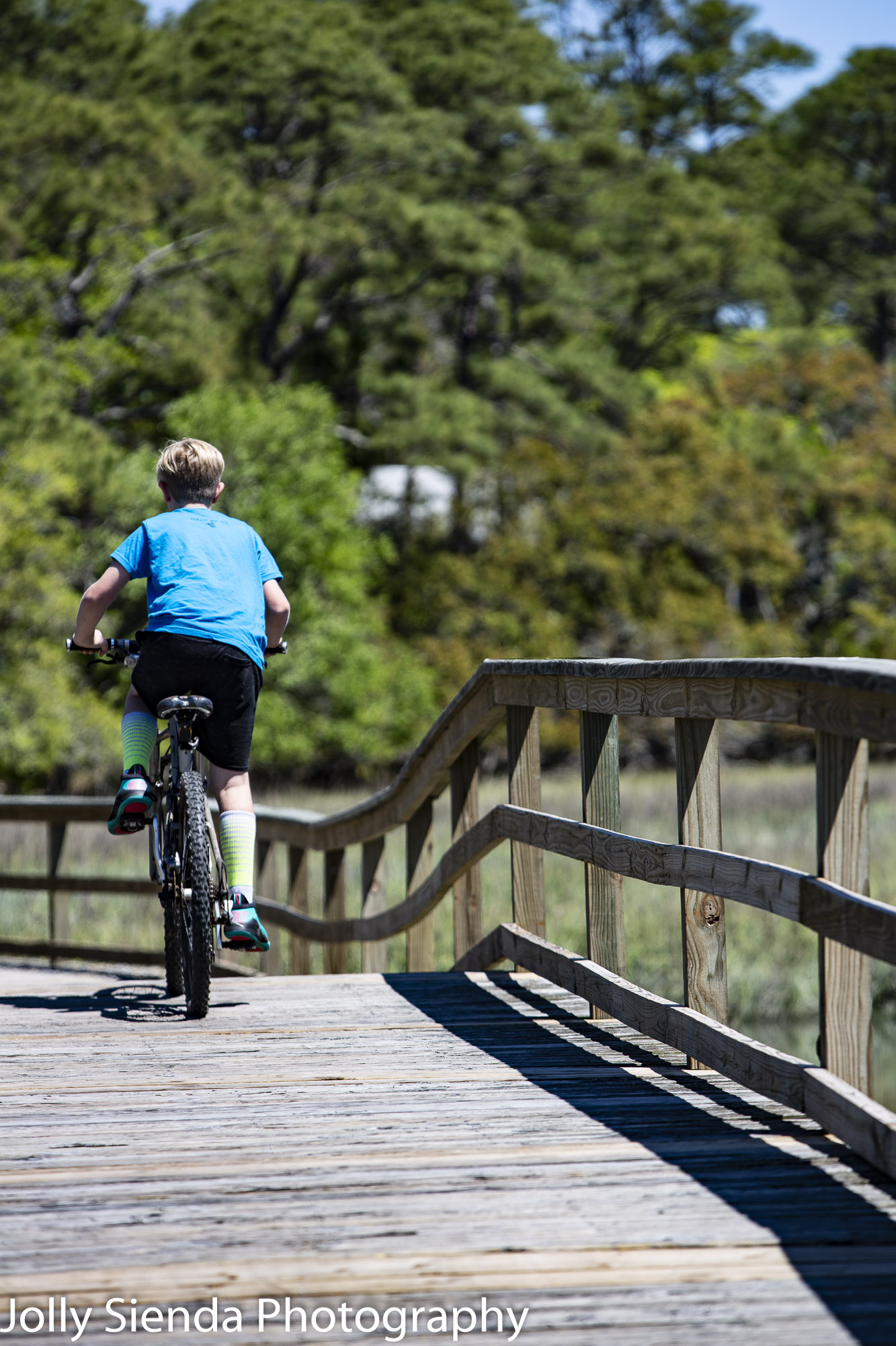 Boy on a bike rides the bridge over the marsh