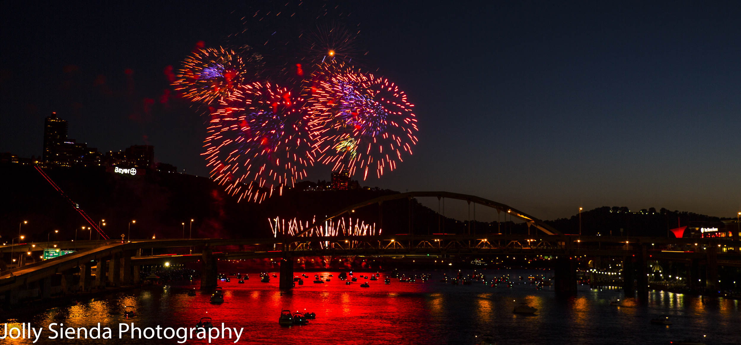 Large cluster firework bursts over the Monongahela River in Pittsburg, PA.