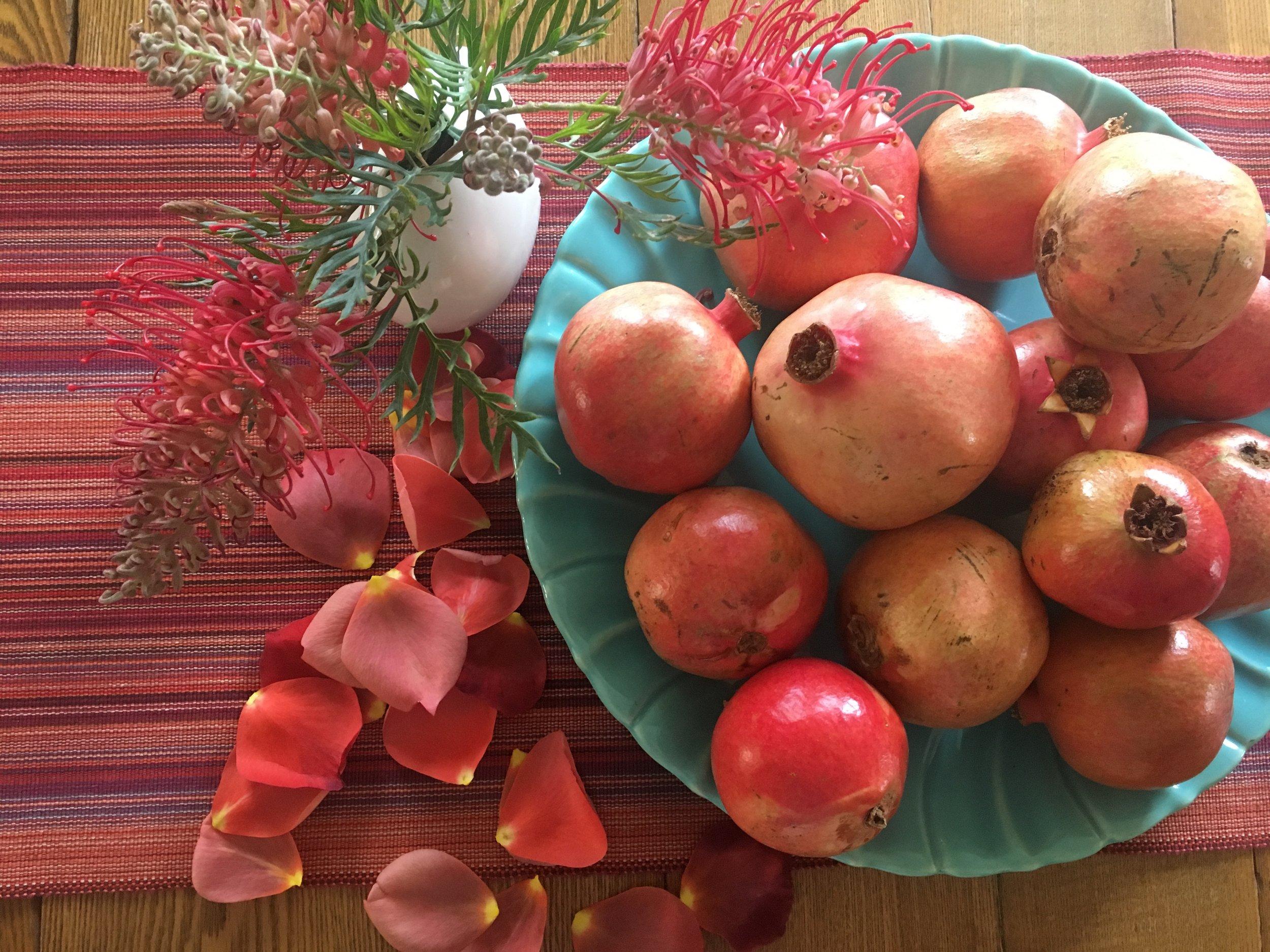 Pomegranates, rose petals and grevillea