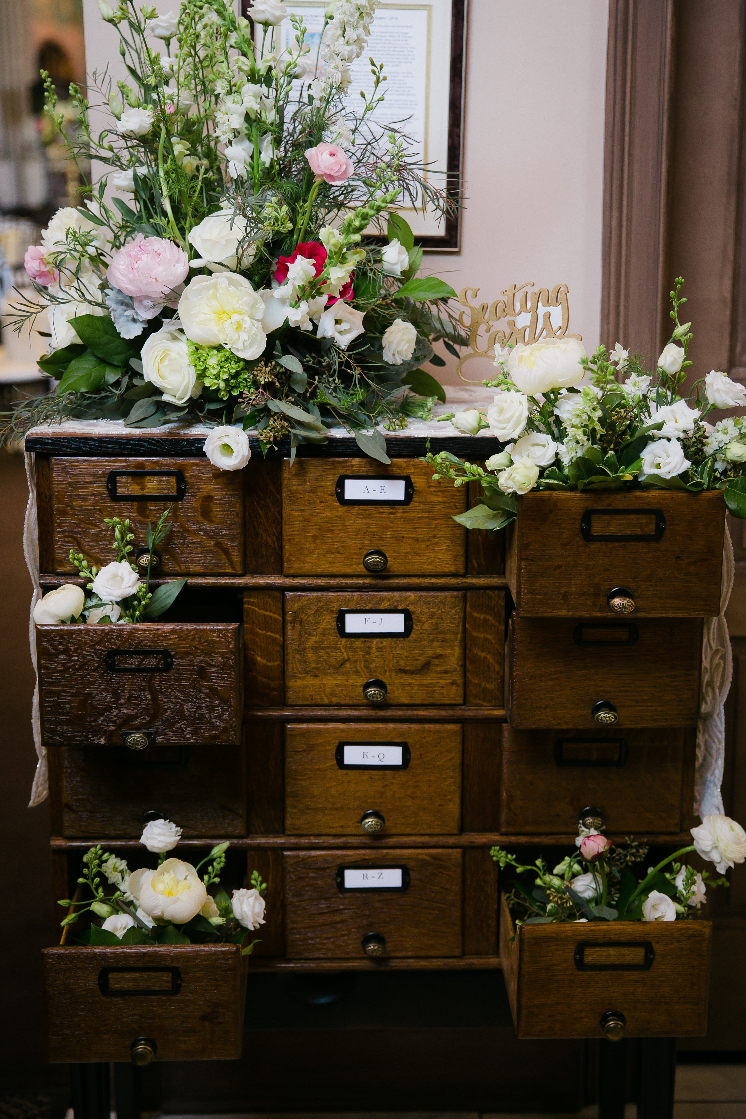 Library card catalogue with pink, white, and red flowers for Monastery Event Center wedding reception in Cincinnati.  Florals by Yellow Canary www.yellowcanaryonline.com