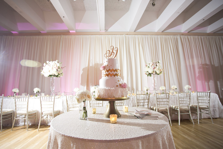 Pink, gold, and white wedding cake and long family style table at wedding reception at The Center in Cincinnati. Florals by Yellow Canary