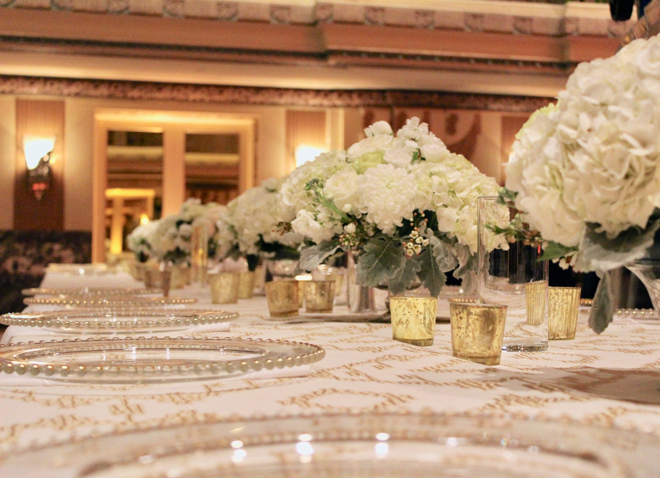 Meredith & Elliot's guests enjoyed a gorgeous reception in a room full of tall, focal arrangements full of white flowers and an assortment of greenery including eucalyptus and silvery lamb's ear.