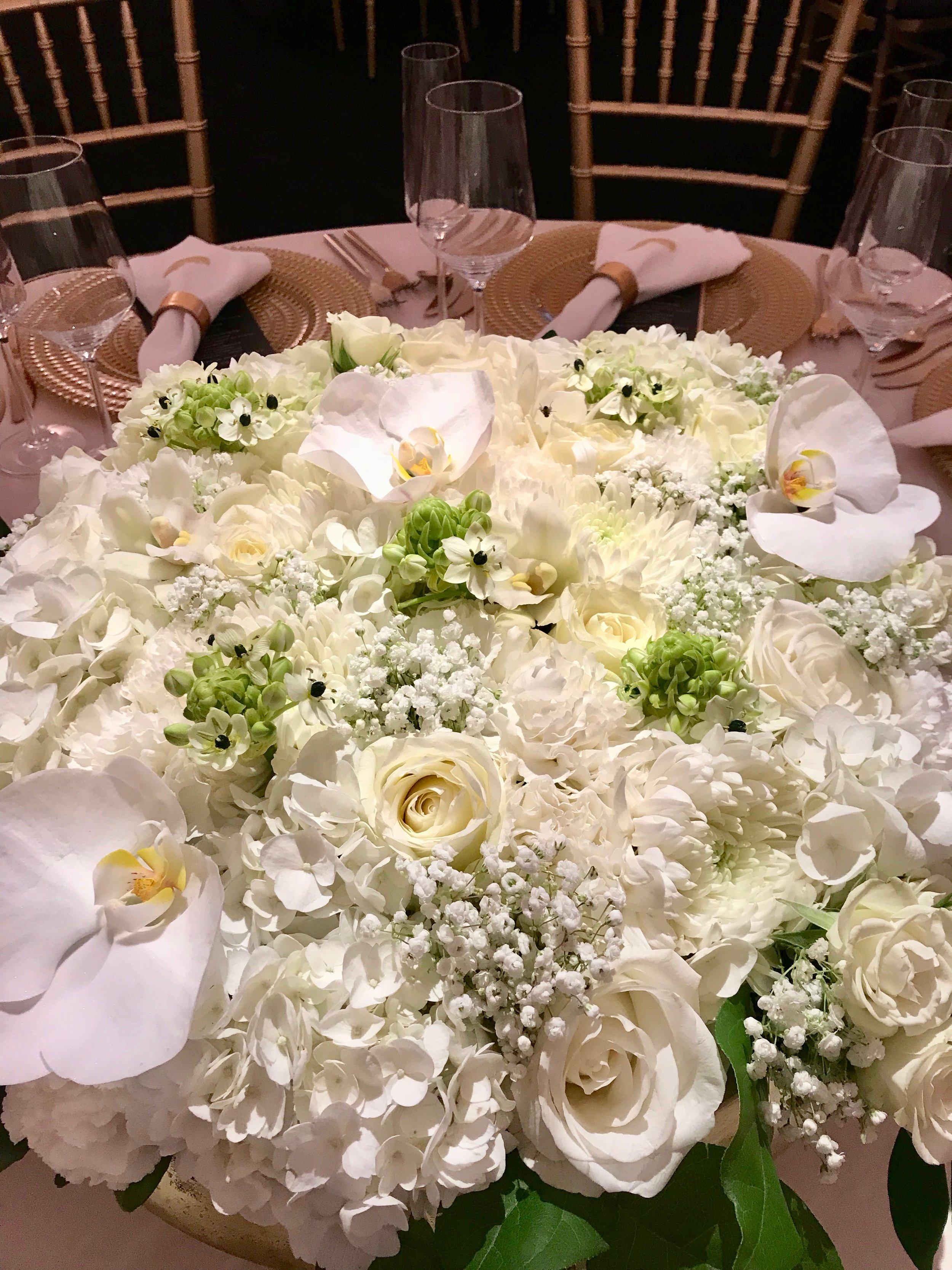 White and green low table arrangement for black tie tented wedding reception