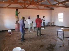 Volunteers from the states and the Jidi football team paint the inside of the school