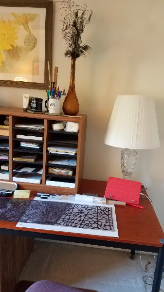 - Behind me is a long table where I work on major Zentangle projects like the transom window film. There is another lamp there and a charging station for items like the iPad and pencil. I have a narrow-shelved case to sort materials for projects.