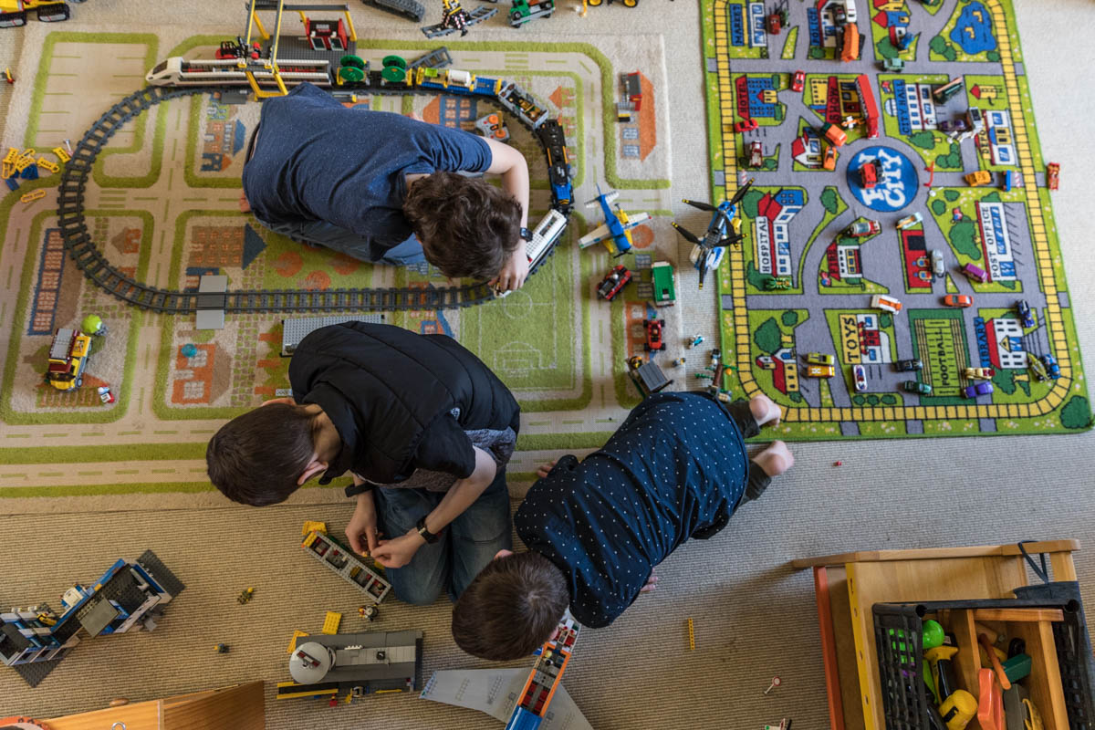 An overhead view of three boys playing Lego and trains at their Geelong home