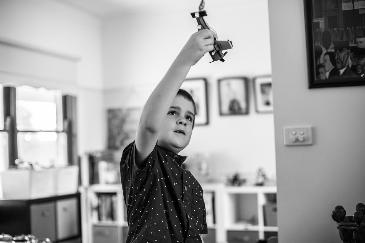 Boy looking up at a toy plane he is playing with