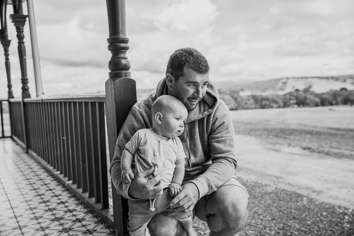 Dad and his baby son looking out to paddocks - Family lifestyle photographer Jan Juc Newtown Geelong Armstrong Creek