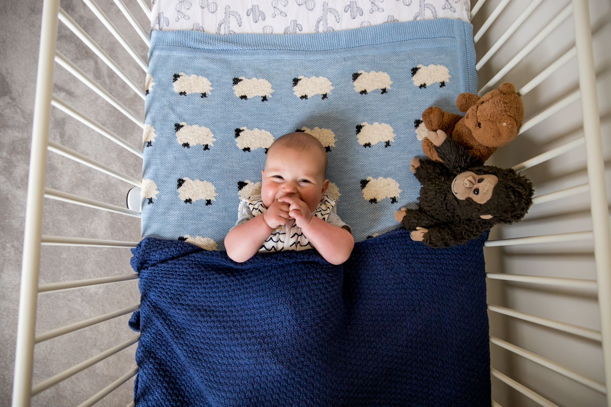 Happy baby ready for bed in cot Armstrong creek family and newborn photographer
