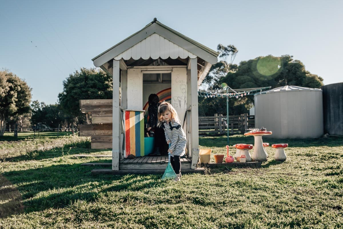 Little girl raking outside her cubby Lauren McAdam Photography Geelong torquay newtown armstrong creek moriac family photographer-1.jpg