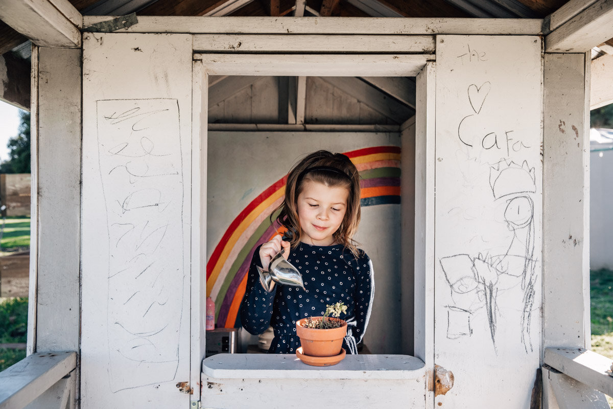 the love cafe - Girl watering flower in cubby