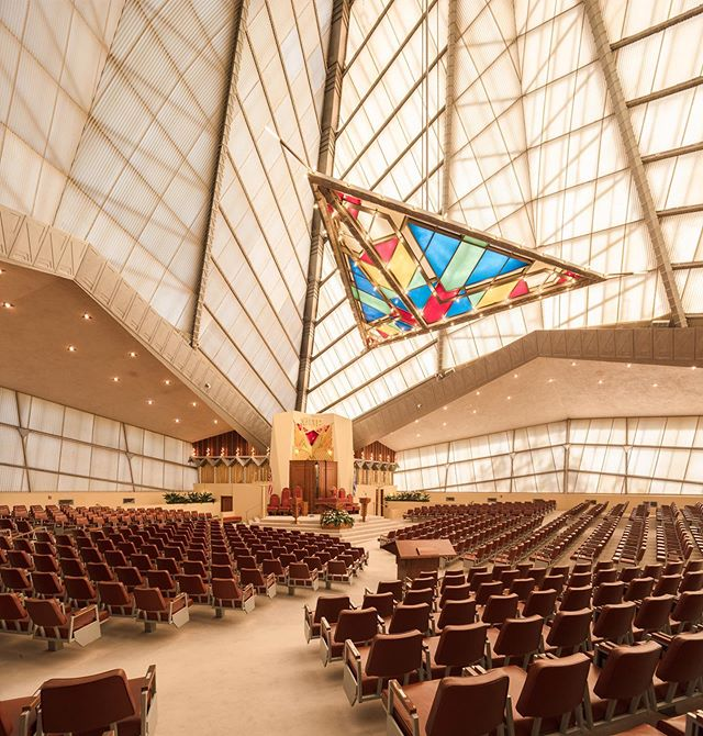 """The interior of Temple Beth Sholom in Elkins Park, PA is an absolute marvel. The Synagogue was designed by legendary architect Frank Lloyd Wright and constructed in 1954. If we're being totally honest... that hanging stained glass would take our Shabbat service daydreaming to new levels.  We spotted this one on @dezeen who writes: Inside, the soaring sanctuary glows majestically, its angled, kaleidoscopic glazed walls and diamond-shaped seating plan facing a forty-foot-tall concrete monolith (representing the stone tablets given to Moses) containing a wooden ark and a dazzlingly colourful, triangular stained-glass """"light basket"""" hanging from the ceiling. . . . . . . . . . . . . . . #architexture #archilovers #archidaily #jewishdesign #architecturedesign #archidesign #architecturelovers #architectural #jewish #judiasm #modernarchitecture #moderndesign #designinspo #designdaily #designoftheday #designlovers #designaddict #interiorarchitecture #midcenturymodern #midcenturyarchitecture #jewishculture #synagogue #synagogues #jewishlife #jewishlifestyle #jewishstyle #frankloydwright #frankloydwrighthouse #interiordesign #stainedglassart"""