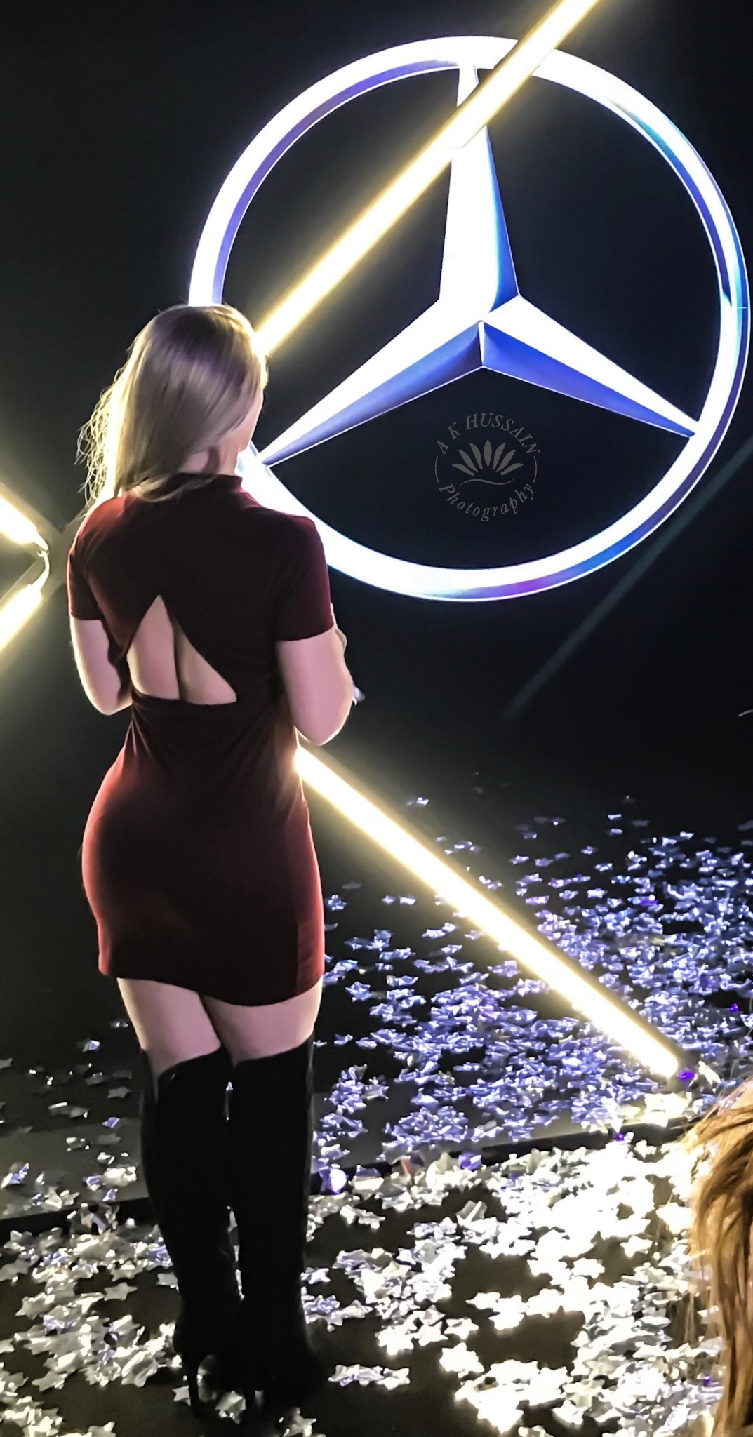 Attendees striking some poses with the illuminated Mercedes logo