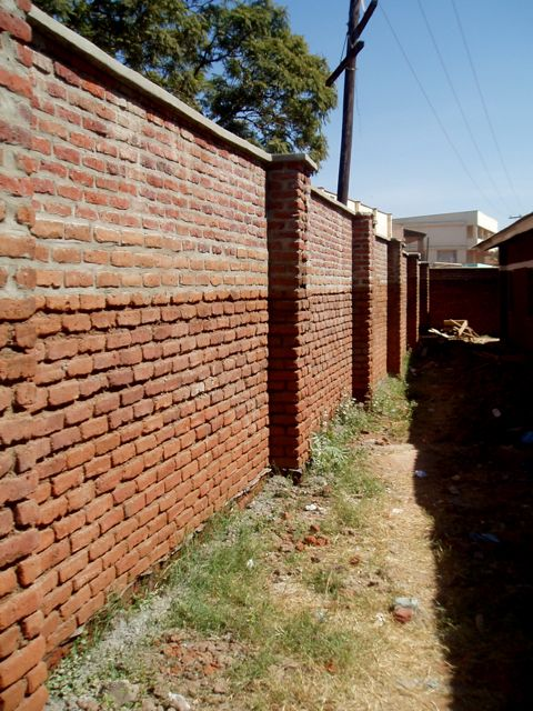 Lilongwe Girls' School Security Wall - In 2014, EGG completed it's first project: a new security wall at Lilongwe Girls' School, in Malawi's capital city.In 2013, Build A School had identified Lilongwe Girls' School as being in desperate need of new facilities. In particular, a broken down security wall was allowing strangers to enter the school from off the busy street that ran alongside the school. The people entering the school were endangering the girls and vandalising school buildings and property.EGG's first project, funded by it's fundraising efforts of 2013, was to re-build the inadequate security wall. The new wall means the girls are safe and at ease whilst at school, as well as having greater privacy and less distractions. The school buildings are harder for strangers to access, meaning the facilities are not abused by passersby. This has provided an environment more conducive to learning.