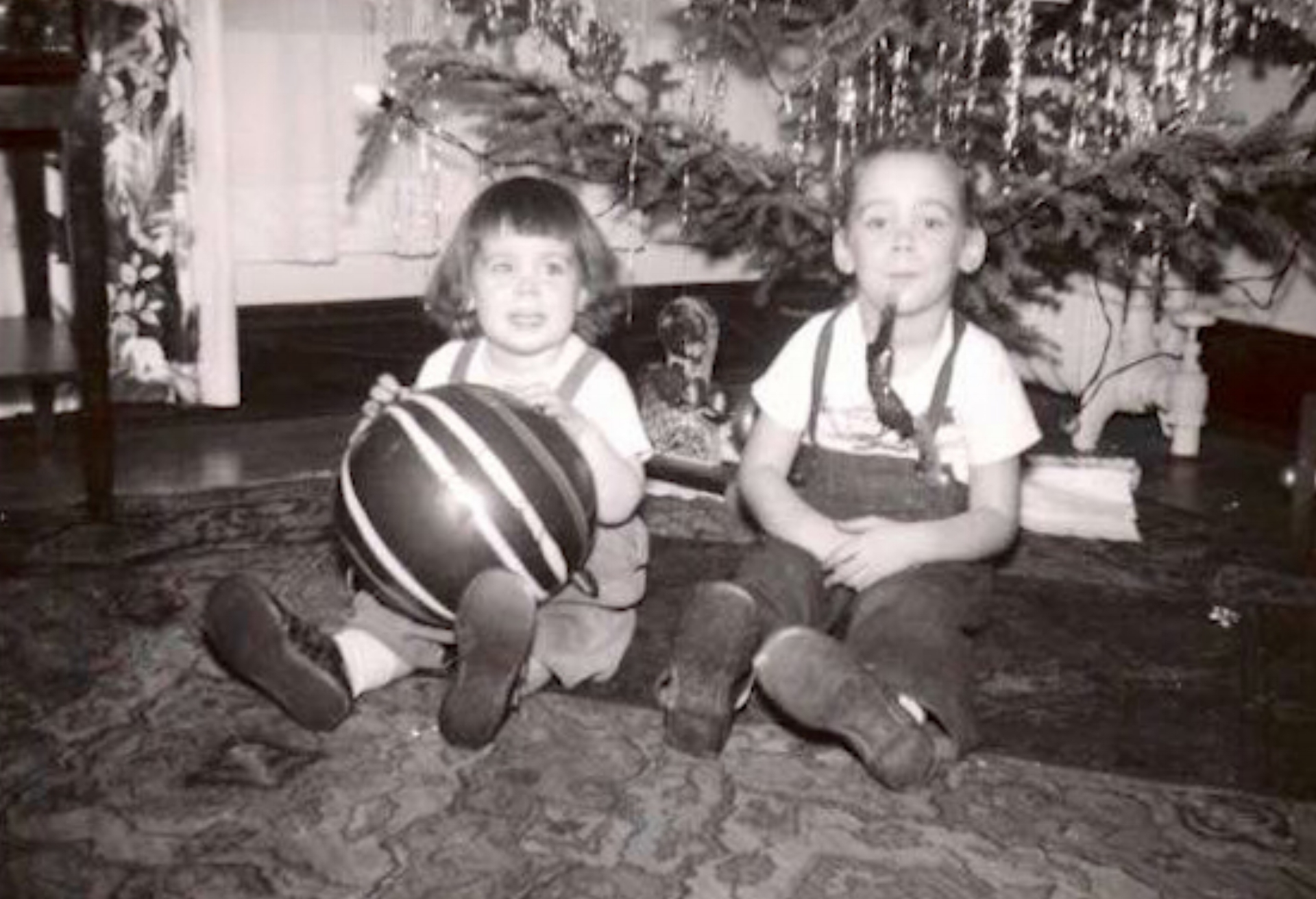 Barbara Ryan (left) and her older sister, Anita Solick Oswald, sit around the Christmas tree in their childhood home on West Madison Street in 1951.