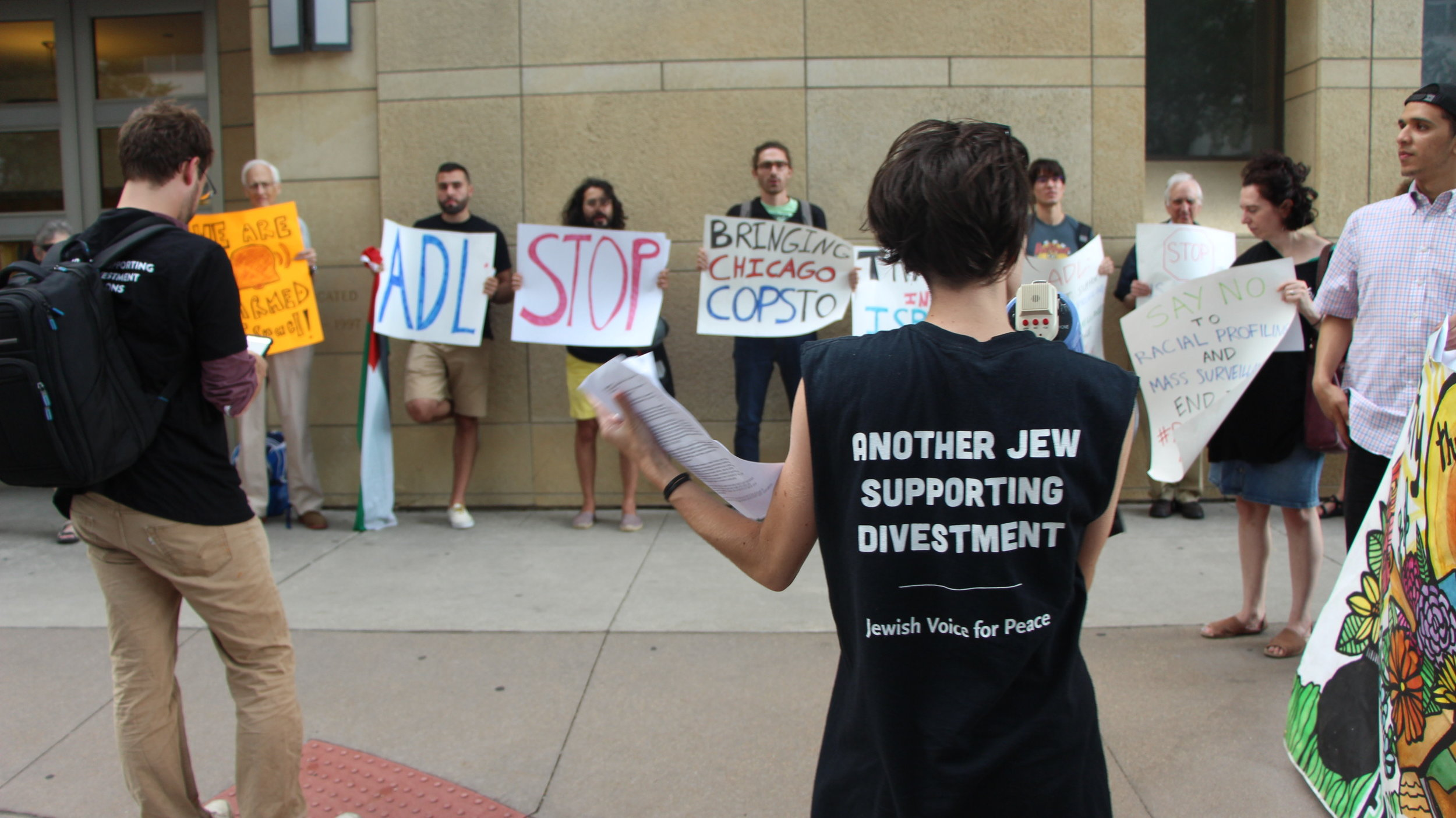 JVP Organizer Scout Bratt speaking to the crowd outside of the Chicago Sinai Congregation to protest the ADL's police exchange program.    Photo by: Pascal Sabino