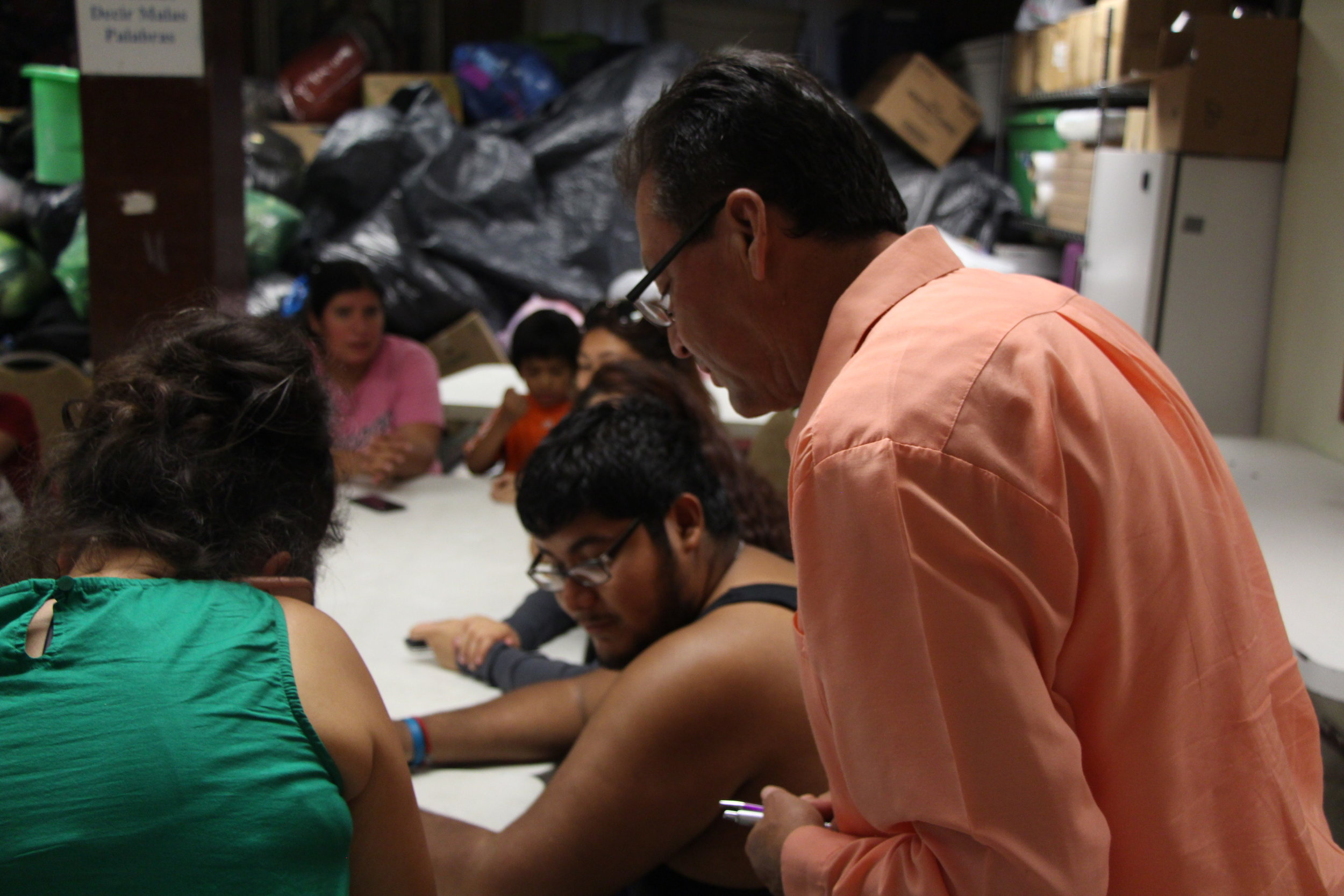 Pastor Ramiro Rodriguez speaks with volunteers before sitting down to a meal after a long day of collecting and sorting donations for the families who lost children and homes.