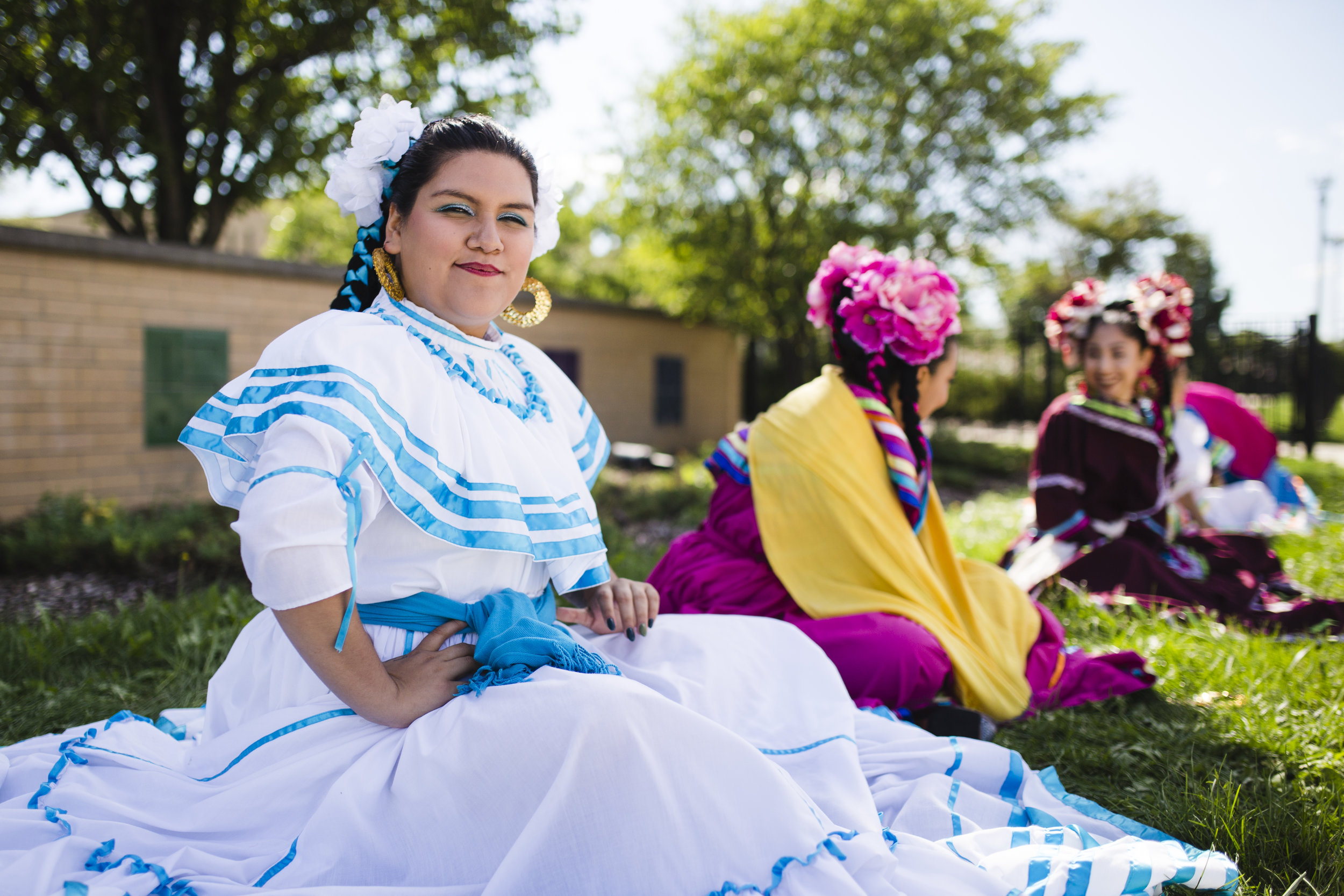 """Ivonne Acosta and her friends rest after dancing for about 1.5 miles during the Mexican Independence Day Parade in Little Village, which was themed """"families belong together."""" """"I feel like [people] are still kind of like afraid in a sense because we have been getting people that have been grabbed [by ICE],"""" said Acosta, who said that the parade was like a break for families in the community. """"They could feel like at least some time to celebrate ... because I know there's some families that are less afraid than others, so like even then, they kind of like feel a little bit more courage to go out and celebrate their culture."""""""