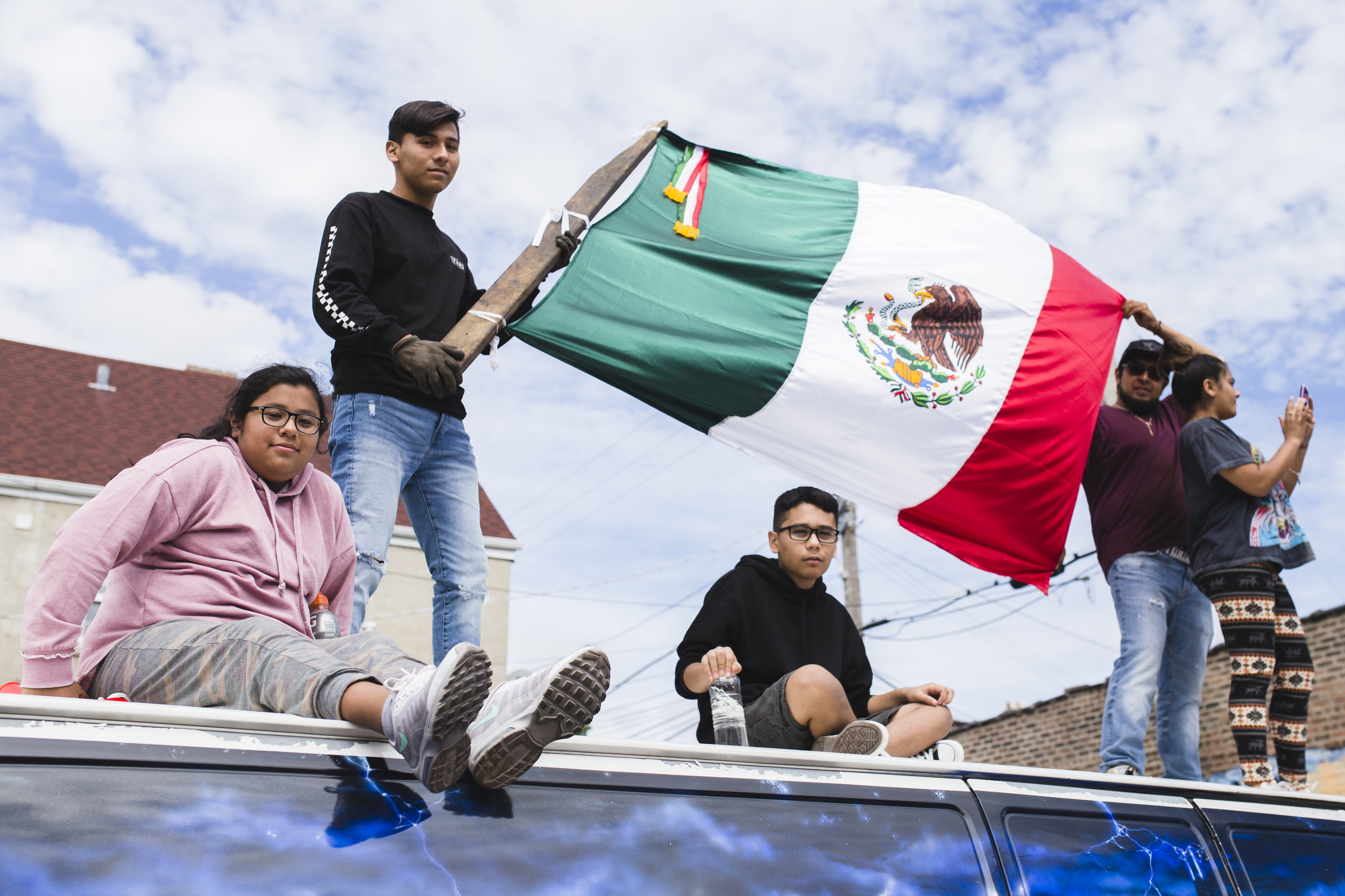 """Lupe Reyes' kids watch the parade from on top of a van. """"We do it every year, come celebrate, you know, our heritage, our blood,"""" said Reyes. """"Twenty-sixth Street, born and raised. I mean, what else can we ask for, you know? [I'm] having a good time. [I] can't wait for next year."""""""