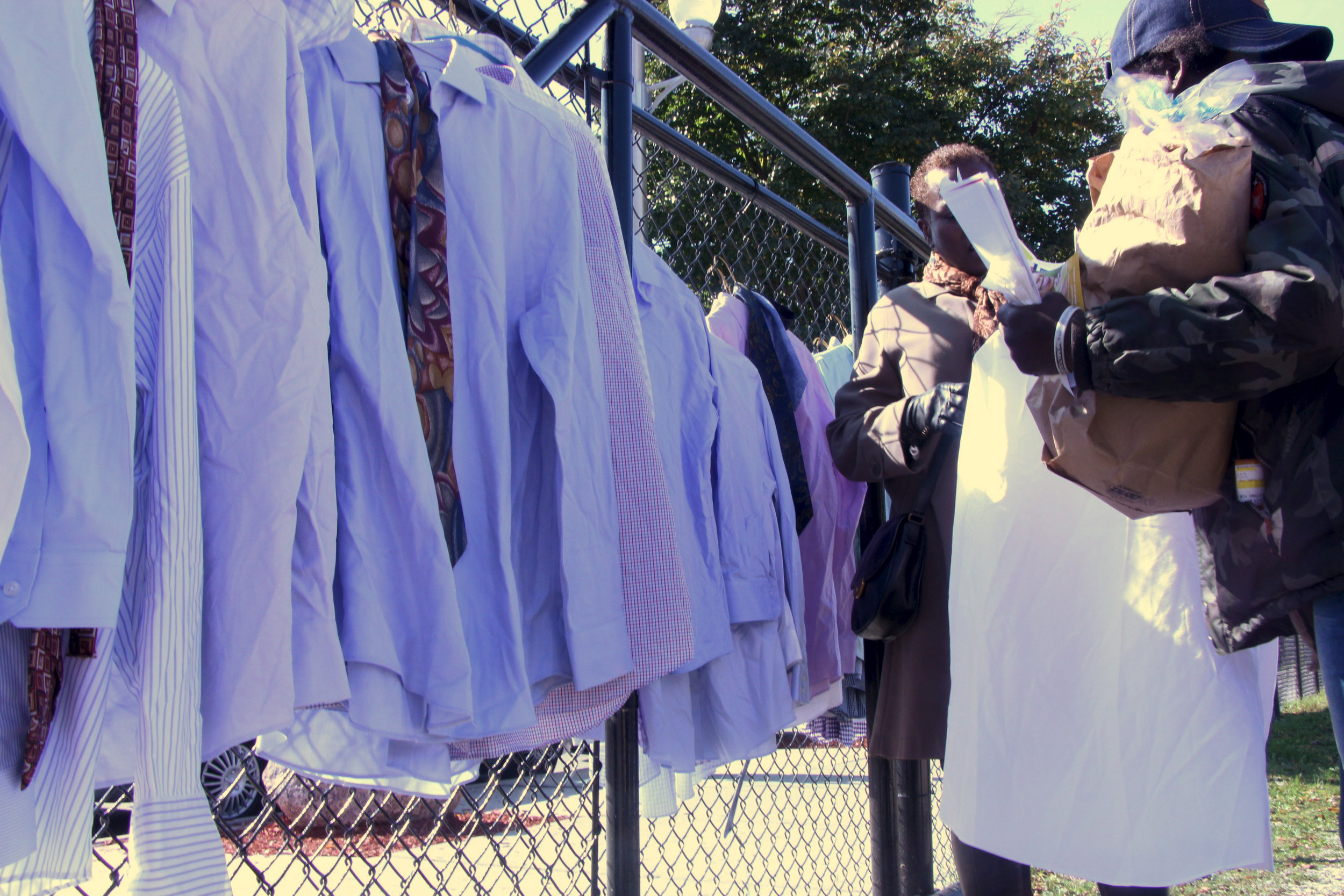 A volunteer from the Living Word Christian Center Prison Ministry helped community members in picking out shirts.