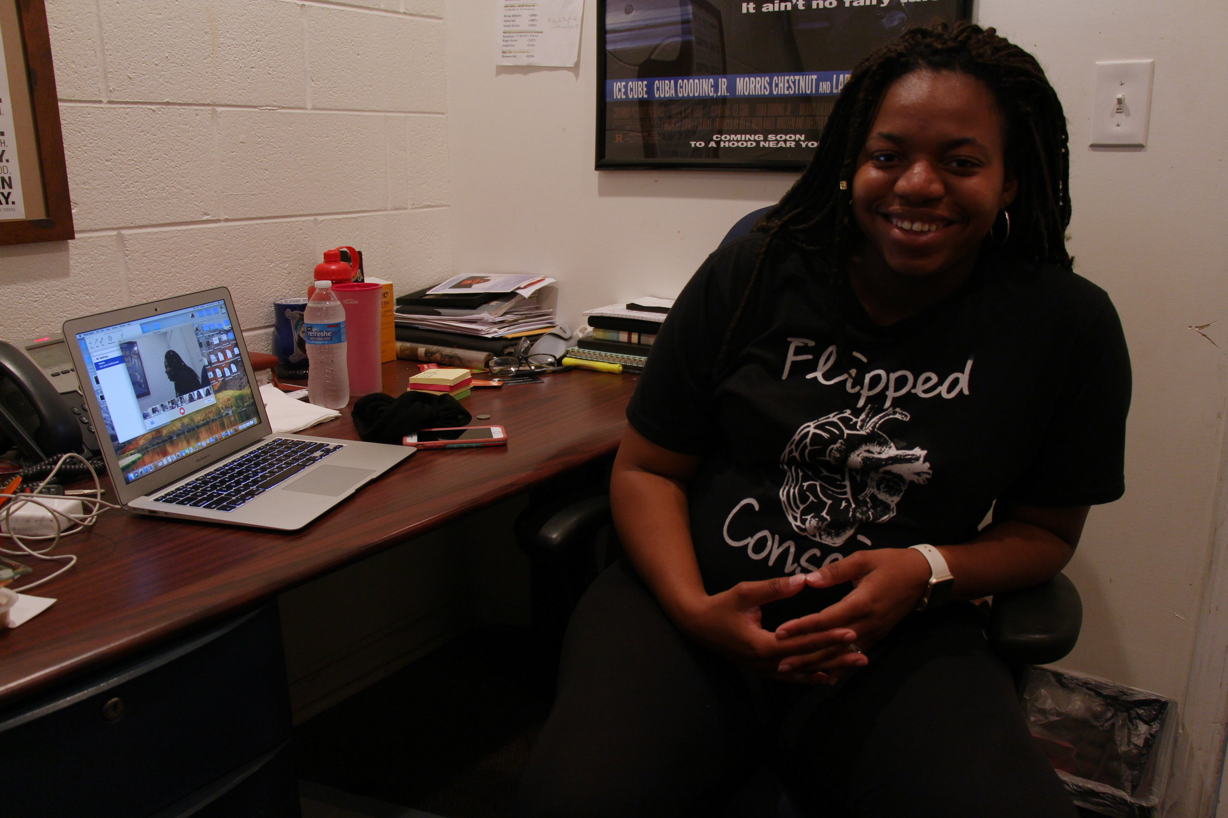"""Kanesha Walker Amaro sitting in her office at the Westside Health Authority. Shirts and hoodies for """"Flipped Conscious"""" are available on her website."""