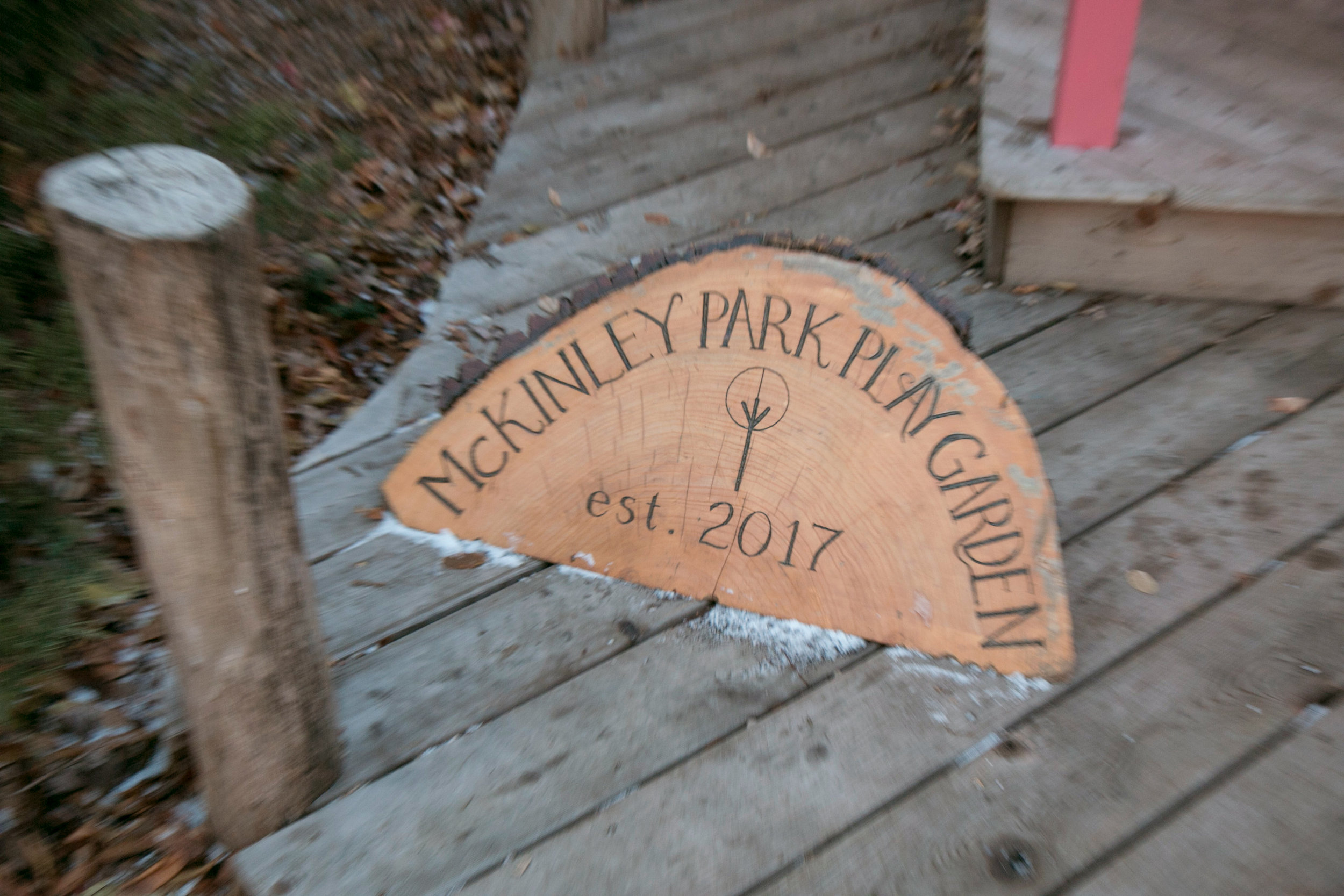 A tree trunk engraving marks the beginning of the McKinley Park Play Garden.