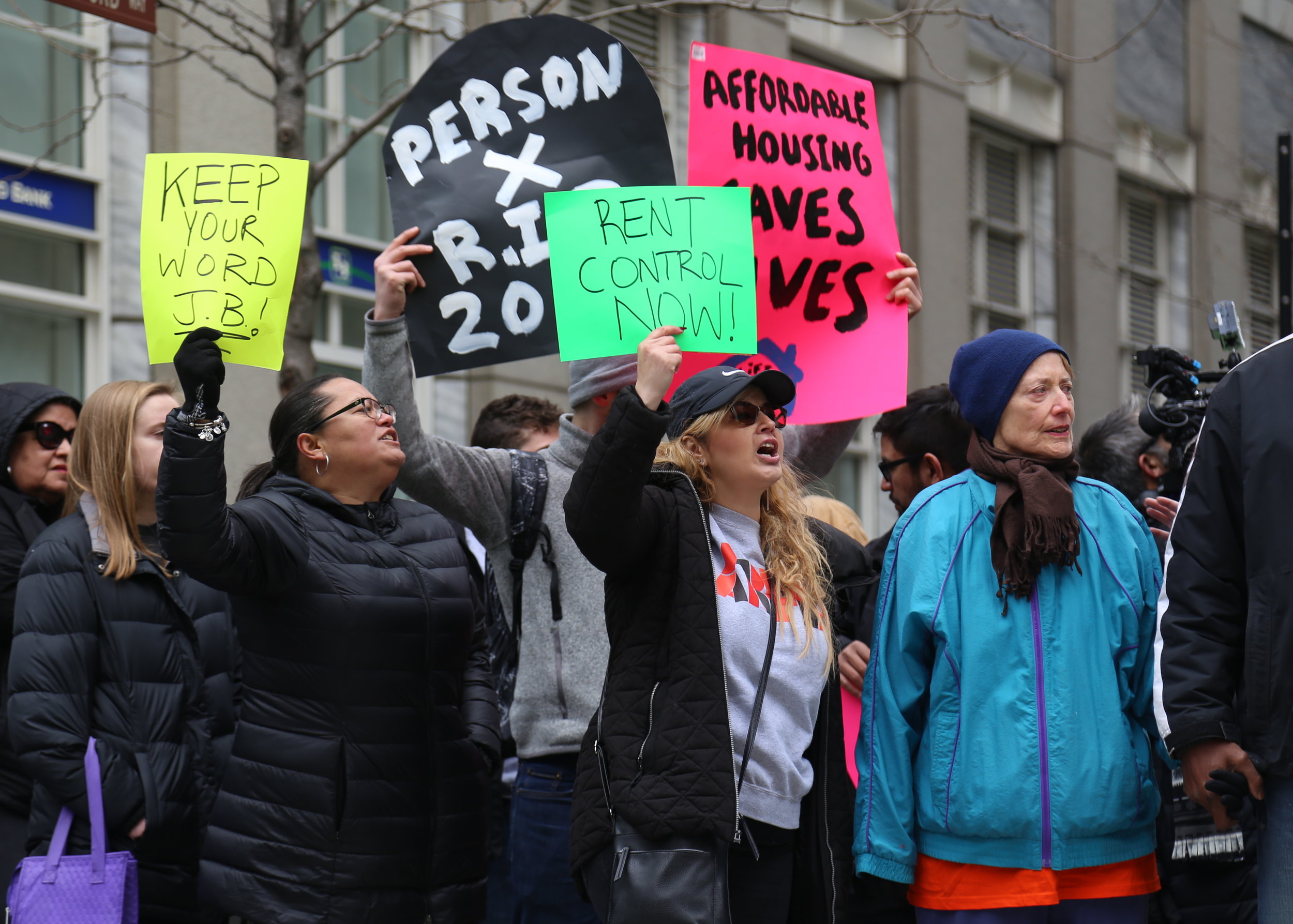Outside the James R. Thompson Center, demonstrators raise signs in protest of Illinois' ban on rent control.