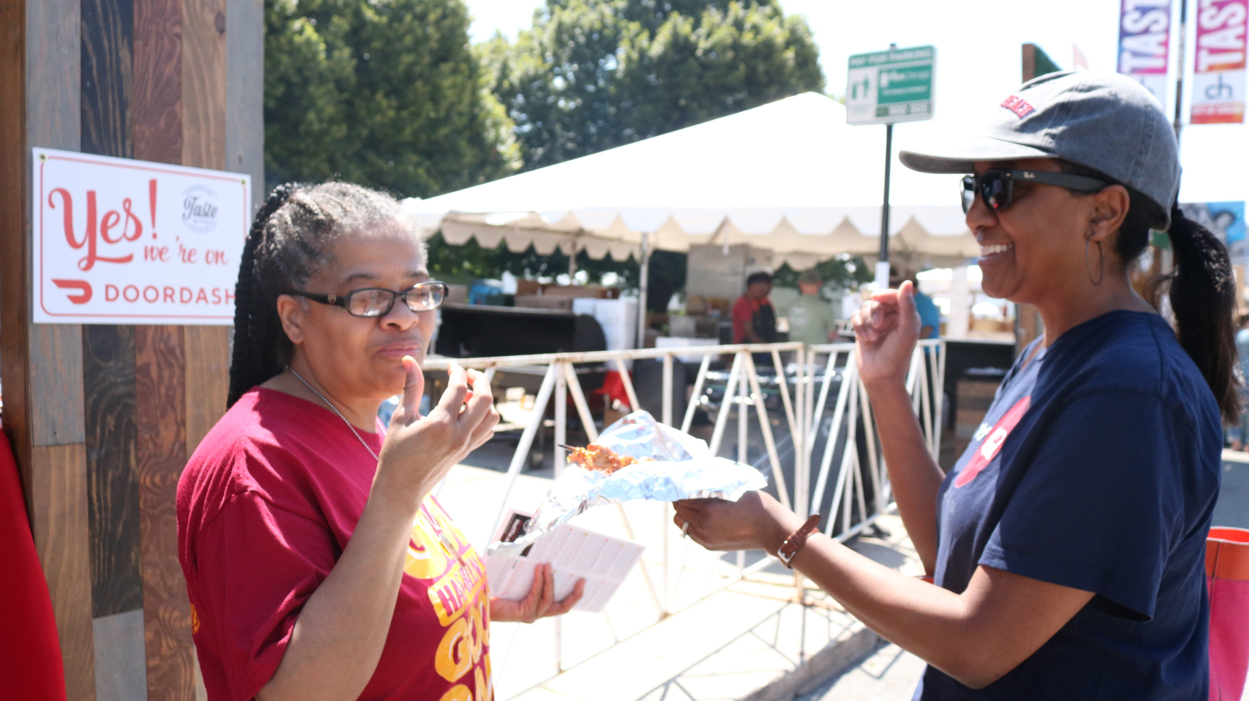 Two first-timers at Grill City sampling the Pork BBQ on a stick. Photo by Clariza Adao