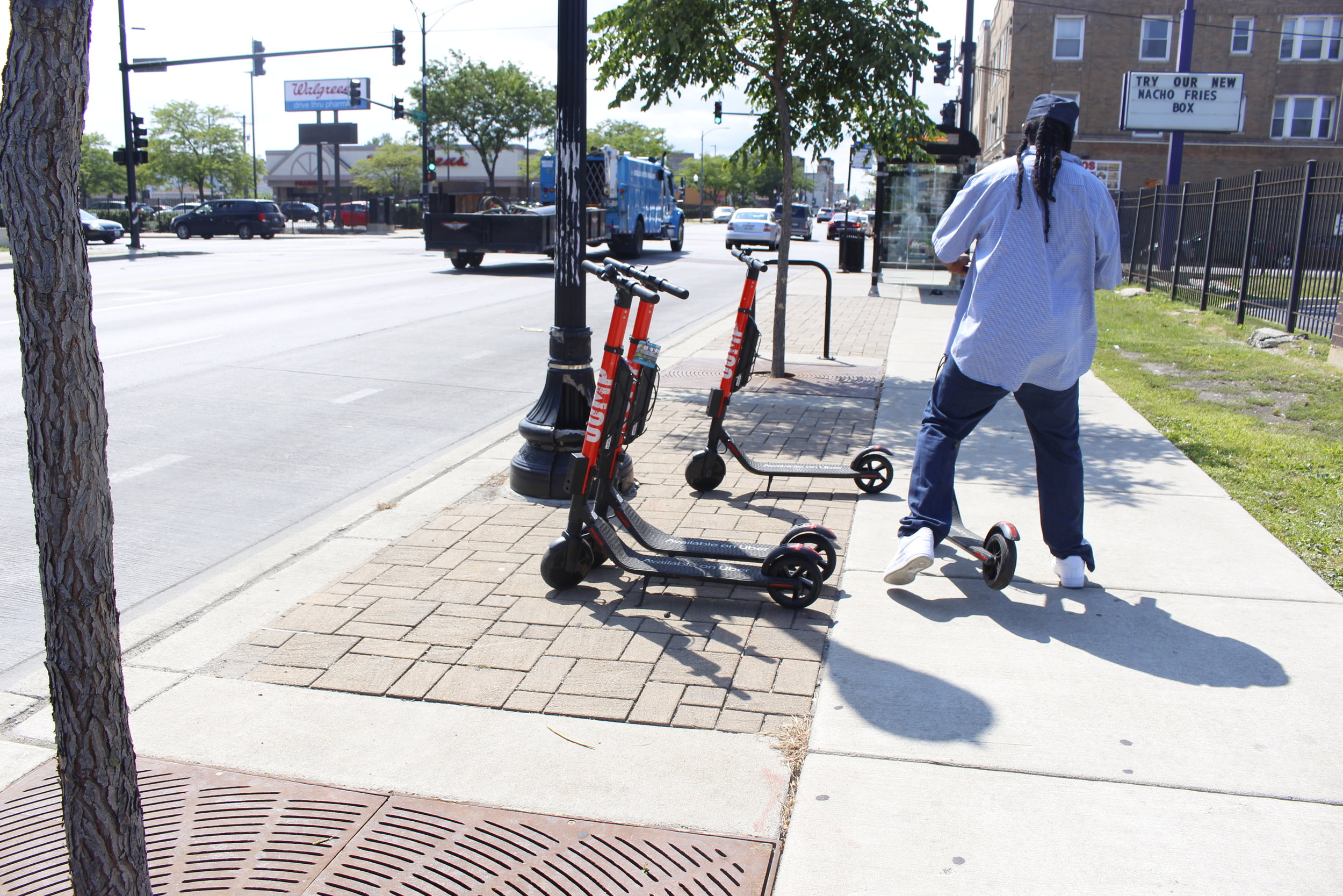 A North Lawndale local taking off on an E-Scooter. Photo by Clariza Adao