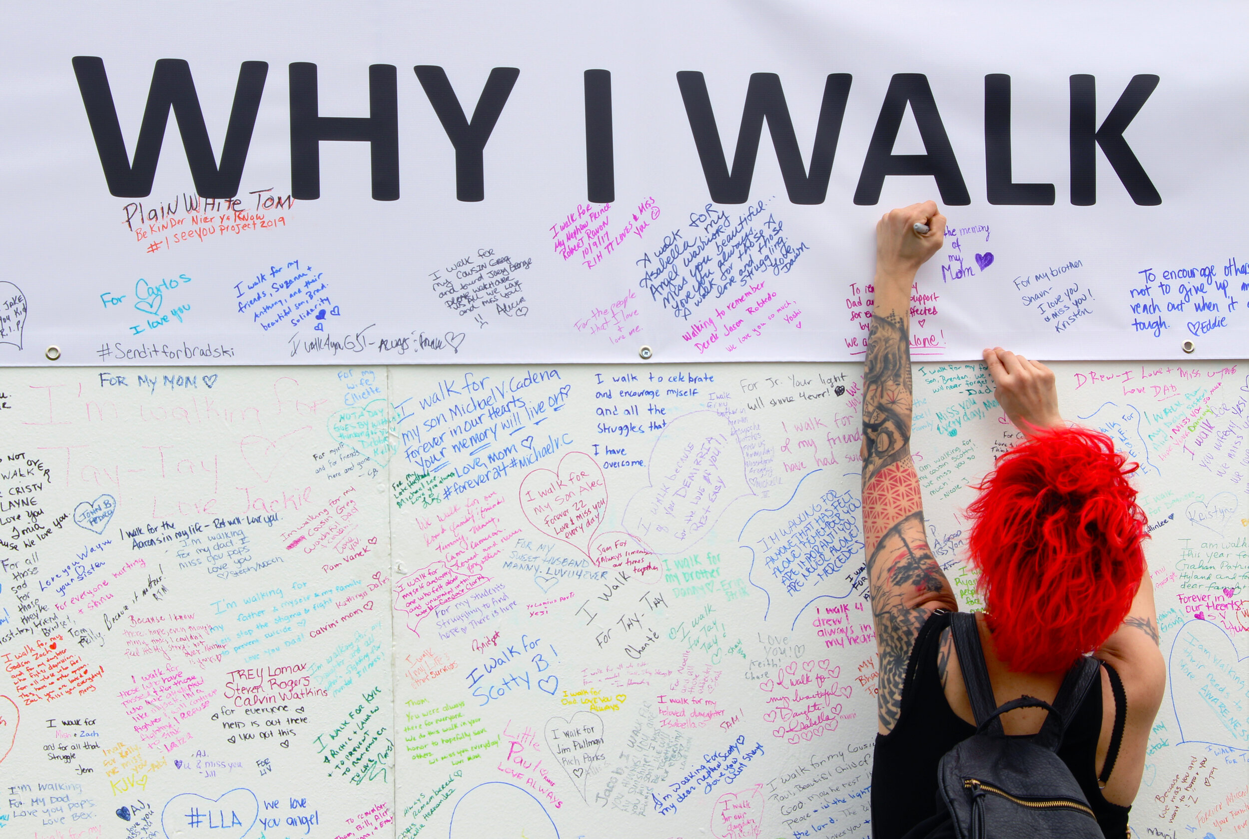 Participant writing a personal message on the  Why I Walk  wall.