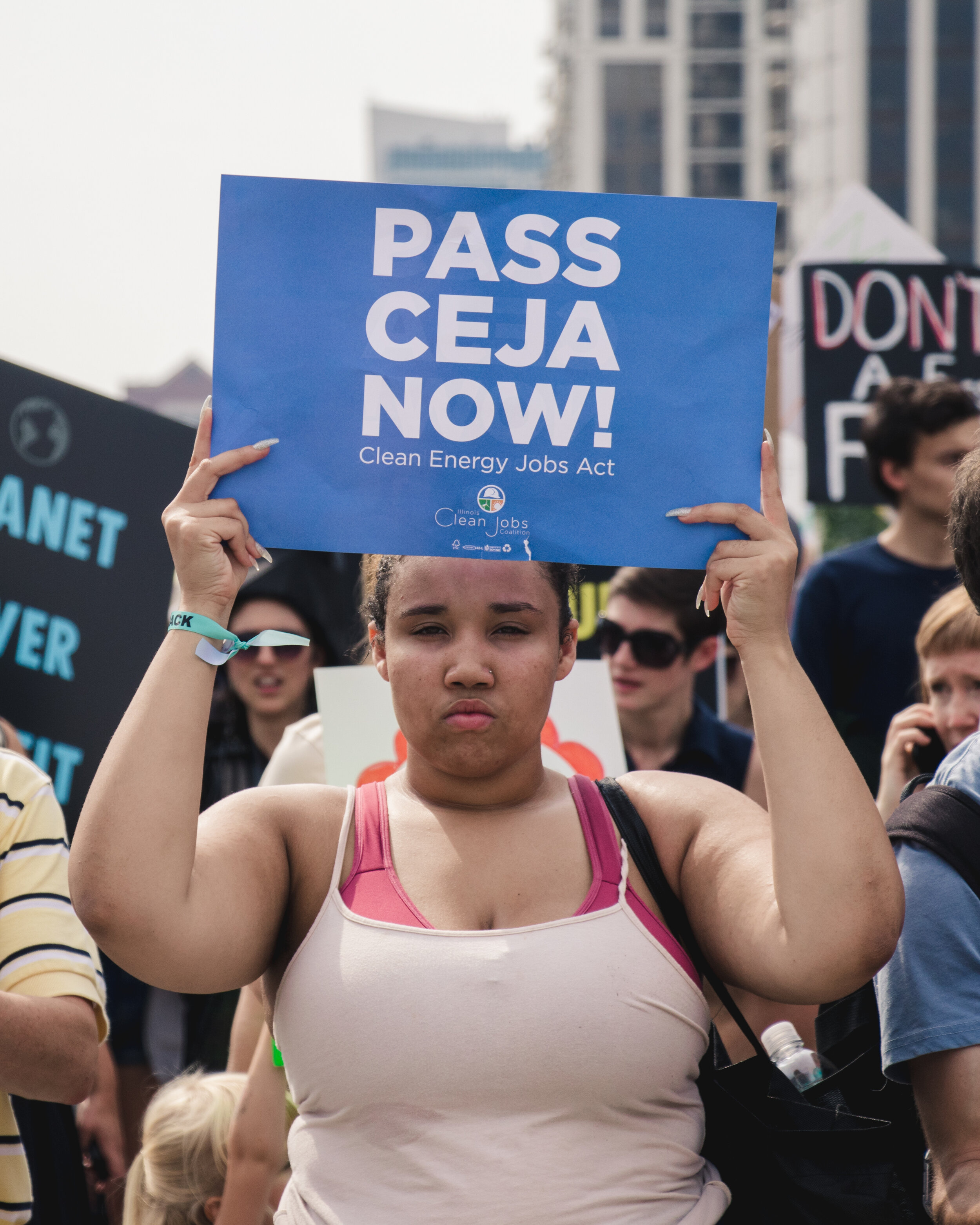 """An organizer hold a sign above her that reads """"Pass CEJA Now."""" The sign is a message for Gov. Pritzker to sign the Clean Energy Jobs Act that would commit Illinois to rely on 100% renewable energy by 2050."""