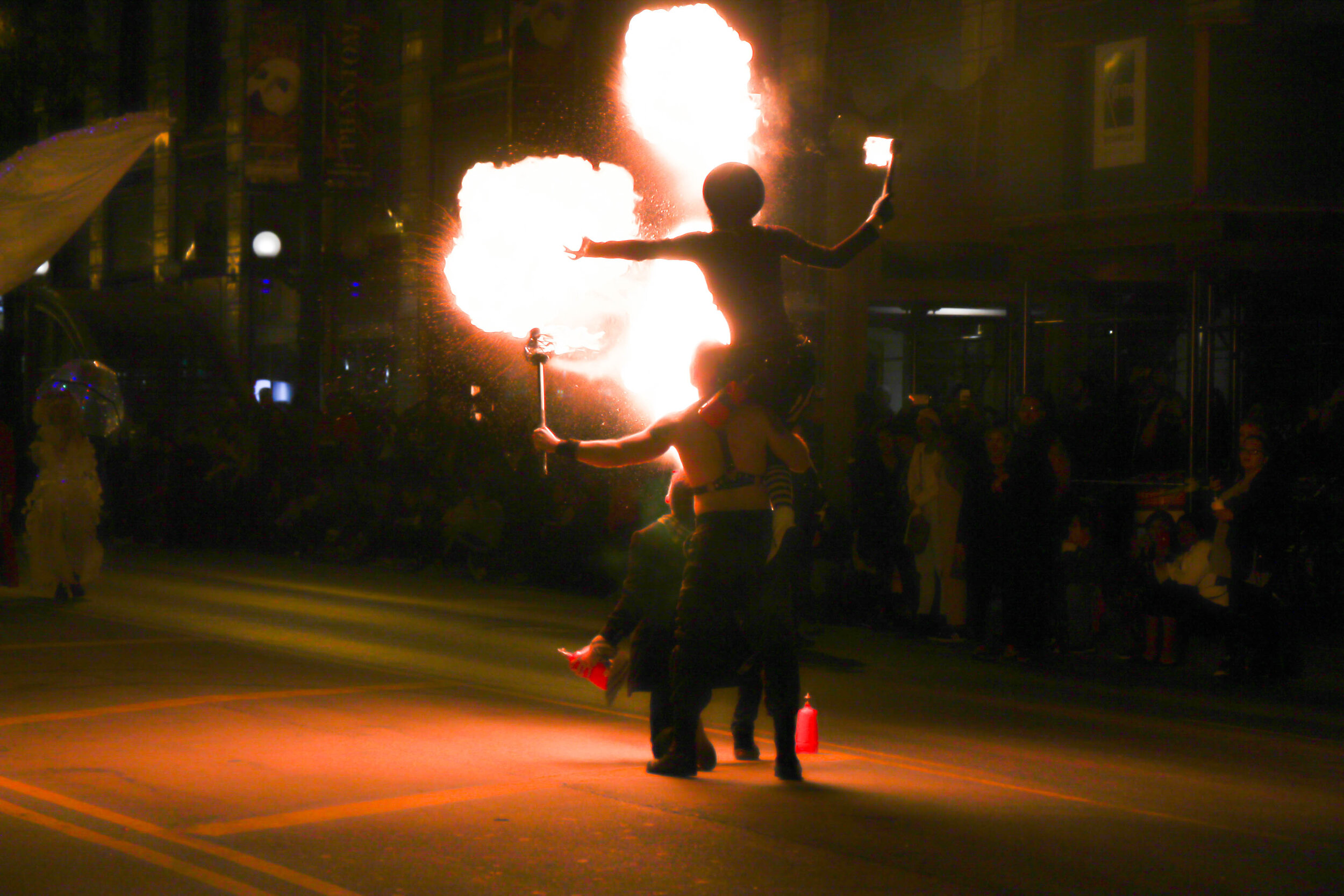 Two performers doing a fire-breathing demonstration at night during the parade.