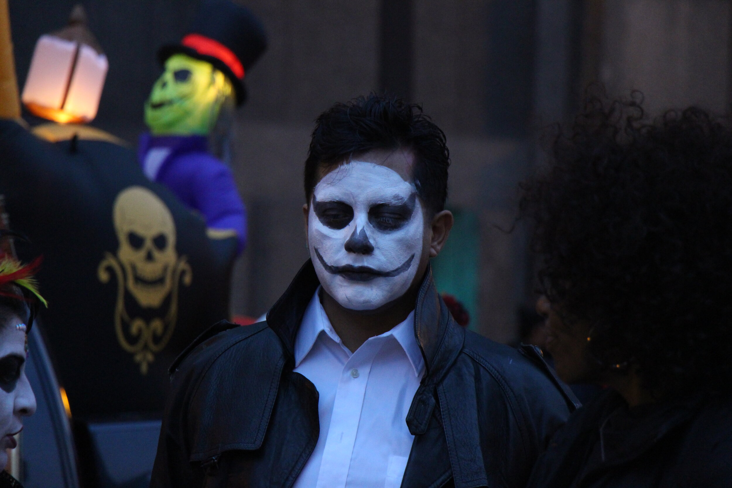 A young man at the Art in the Dark parade with his face is painted white and his eyelids and lips are covered in black .