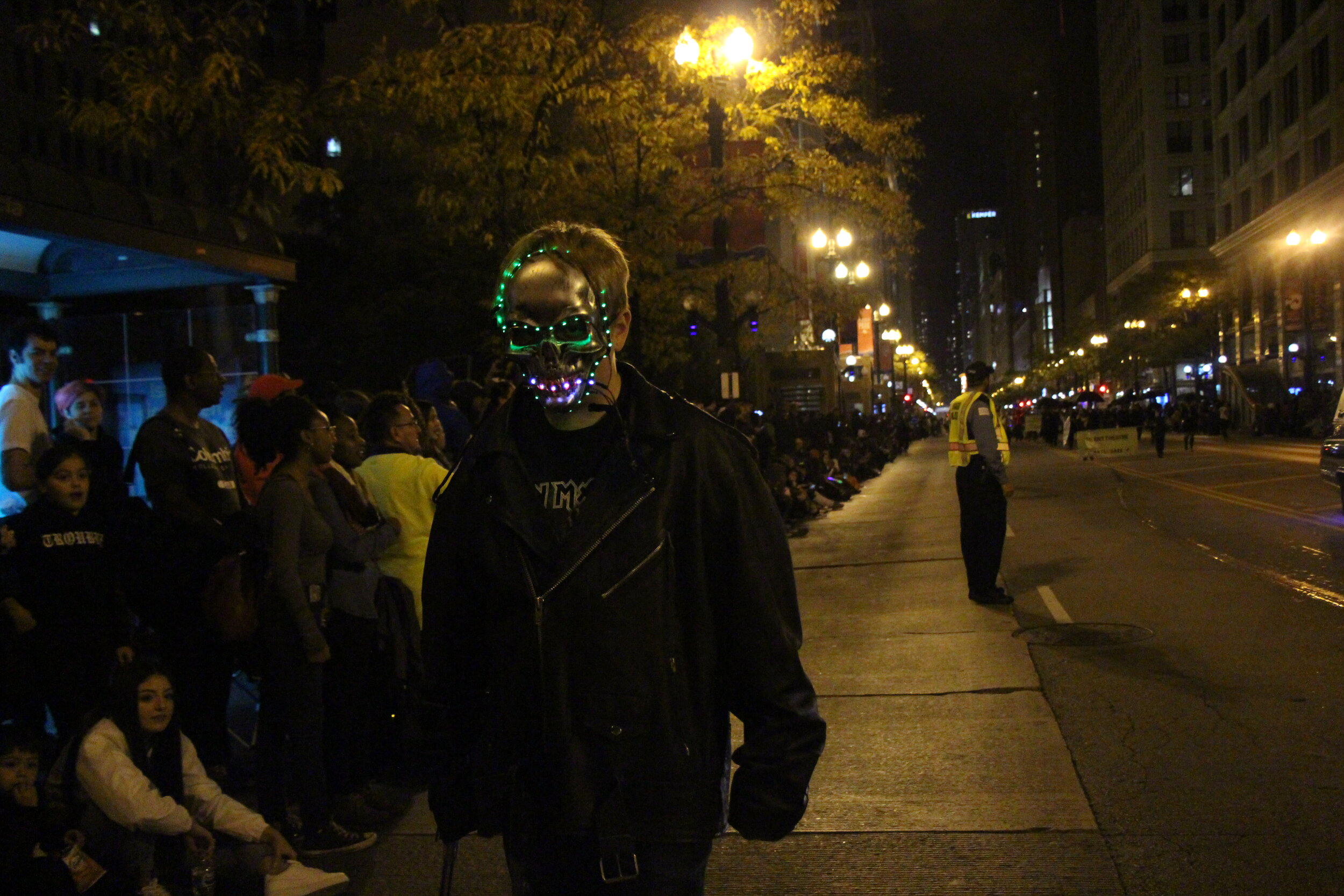 Attendee costume stands out from the crowd wearing a glowing purple and green mask.