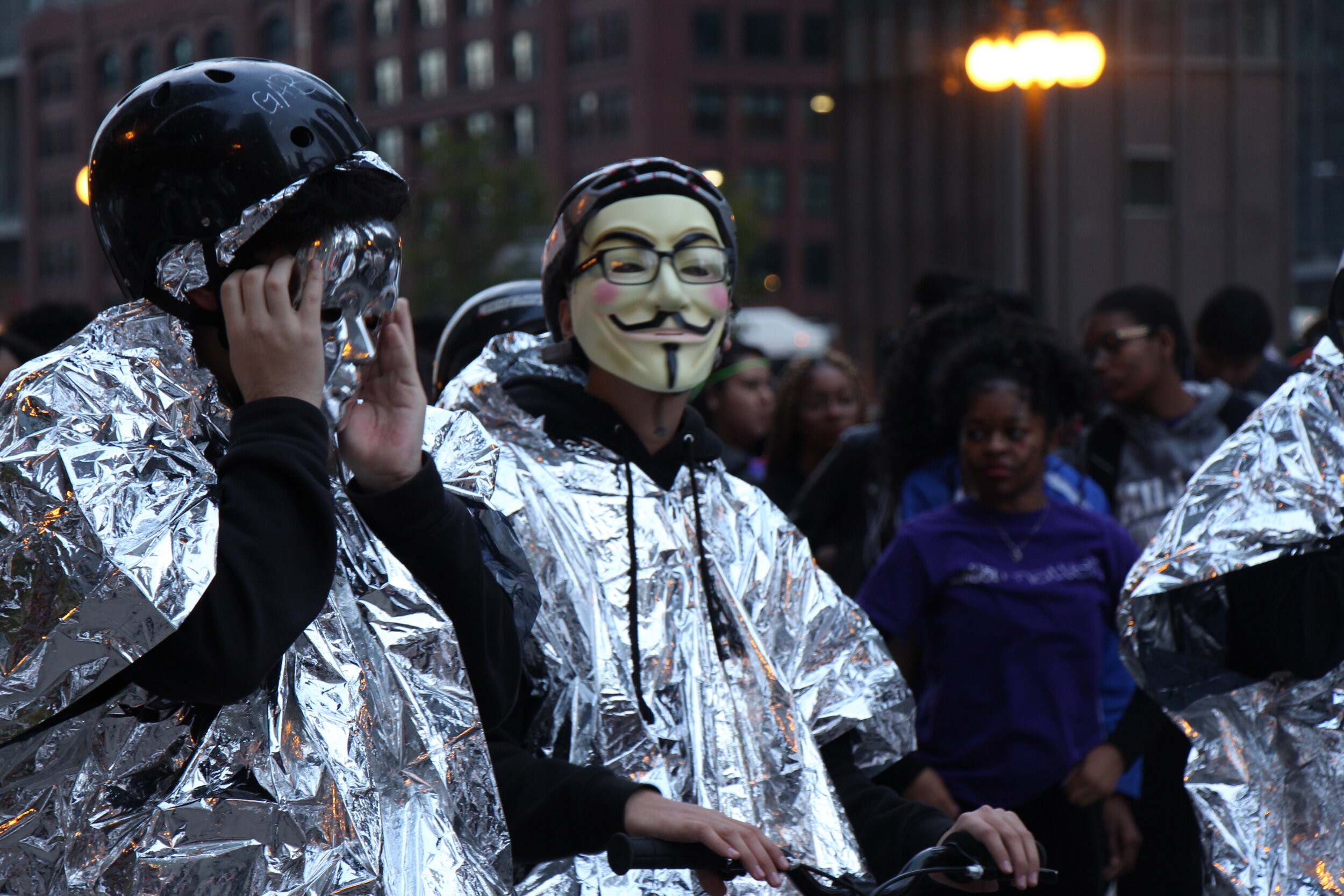A group of students from After School Matters present themselves wearing masks while riding bikes during the parade.