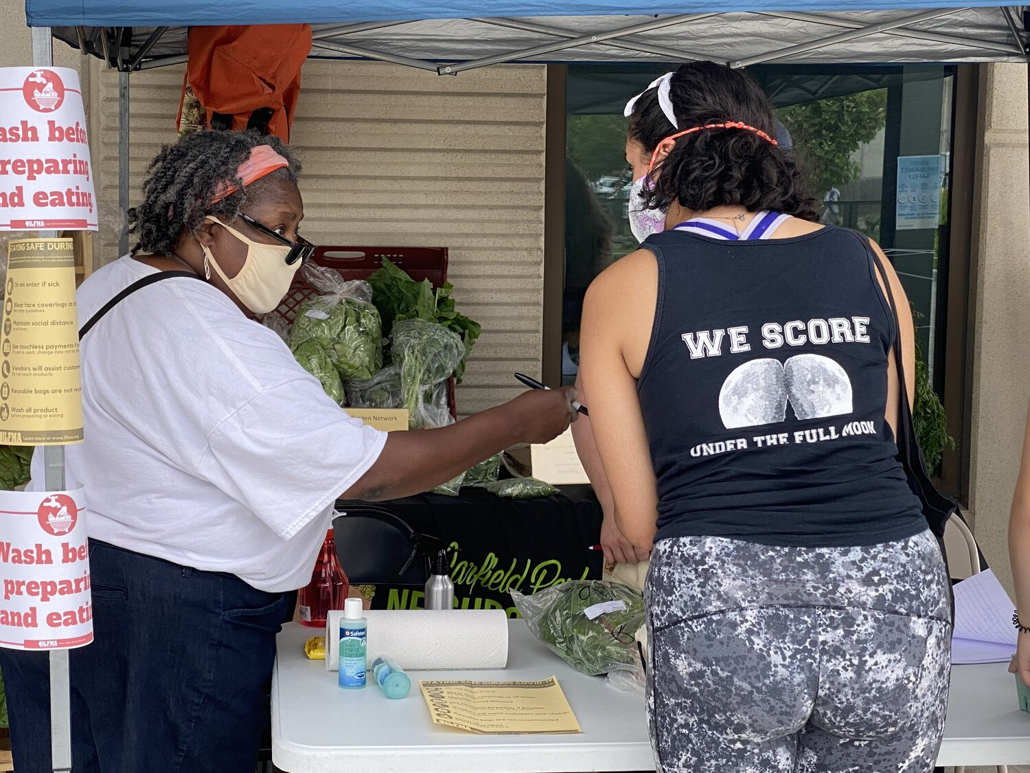 The Wellness Coordinator at The Garfield Park Community Council Angela Taylor (left) helps a customer (right) with their purchase at The Garfield Park Neighborhood Market on July 11. 2020. Photo by Mariah McBride.