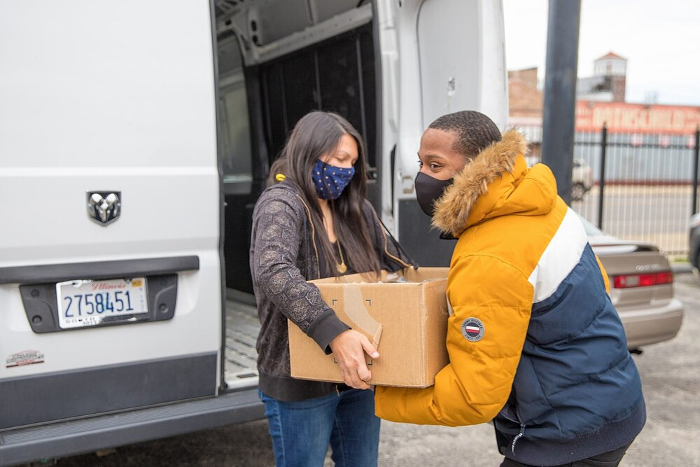 ChiFresh Kitchen founder Camille Kerr hands off a box of fresh meals to worker-owner Daniel McWilliams (Source: ChiFresh Kitchen Facebook)