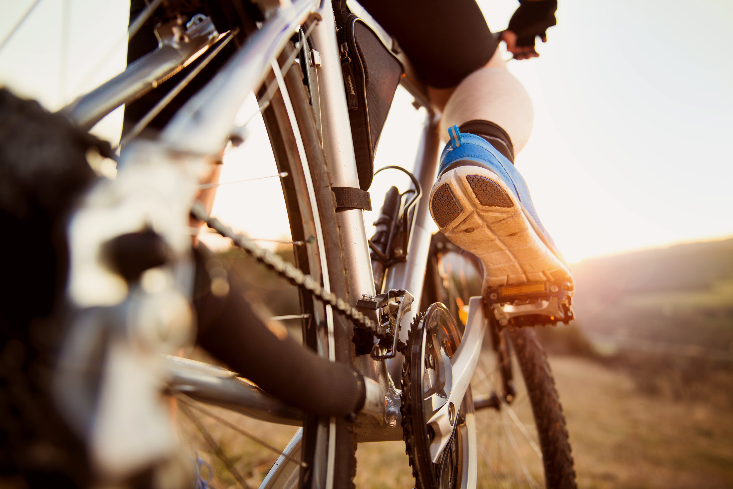 graphicstock-detail-of-cyclist-man-feet-riding-mountain-bike-on-outdoor-trail-in-sunny-meadow_r01mTenbZ.jpg