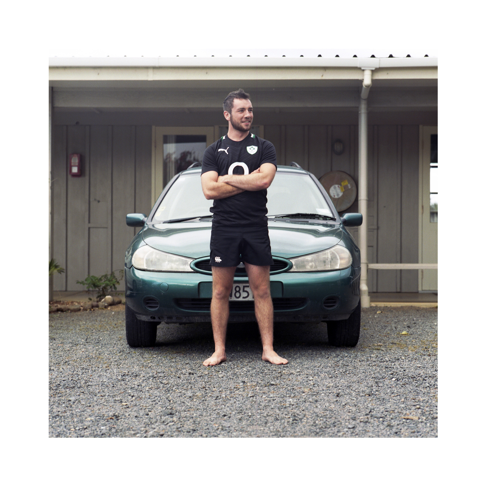 Mikey Davidson from Ballinderry, Northern Ireland - Hone Heke Lodge, Kerikeri.  At this stage in his journey Mikey is for all intents and purposes stranded in Kerikeri.  He stands in front of his car which has just failed it's WOF (Warranty of Fitness) and requires $1,700 worth of repairs to become road worthy.  In order to obtain the money to fix the car he is waiting patiently for fruit picking work in the area.  Once the car is fixed Mikey will recommence his journey exploring Aotearoa.