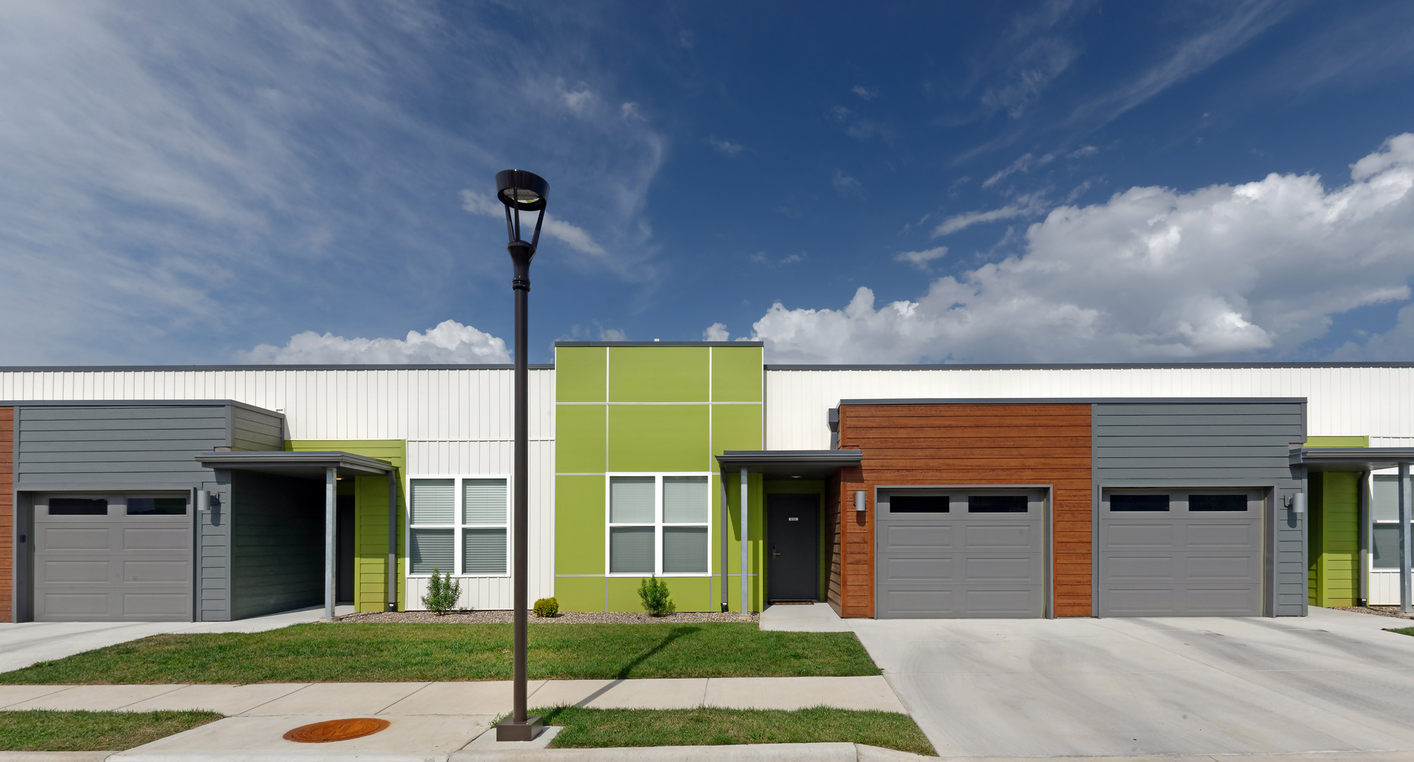 Modern apartment community in Springfield, Missouri featuring a dynamic mix of modern townhomes, one, two, and three bedroom apartments over various building types; all brought together by a bold and progressive color and material palette.  Feturing modern amenities including pool with cabana, indoor fitness, with gated security.