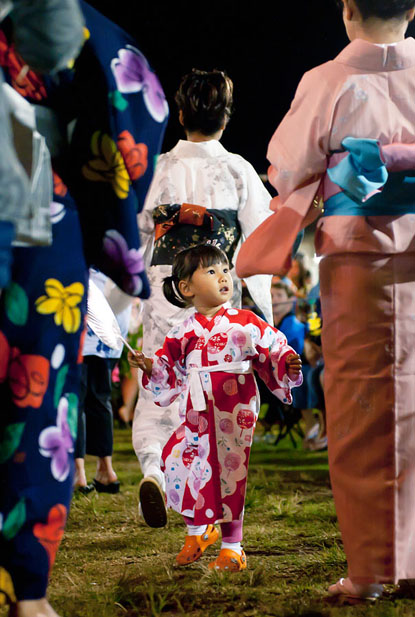 A young girl participates in her first Bon Odori, or Bon Dance, at the Makawao Hongwanji Mission in Makawao, Hawaii. Bon Dances are performed during Japanese Obon Festivals to welcome and honor the spirits of deceased family members.